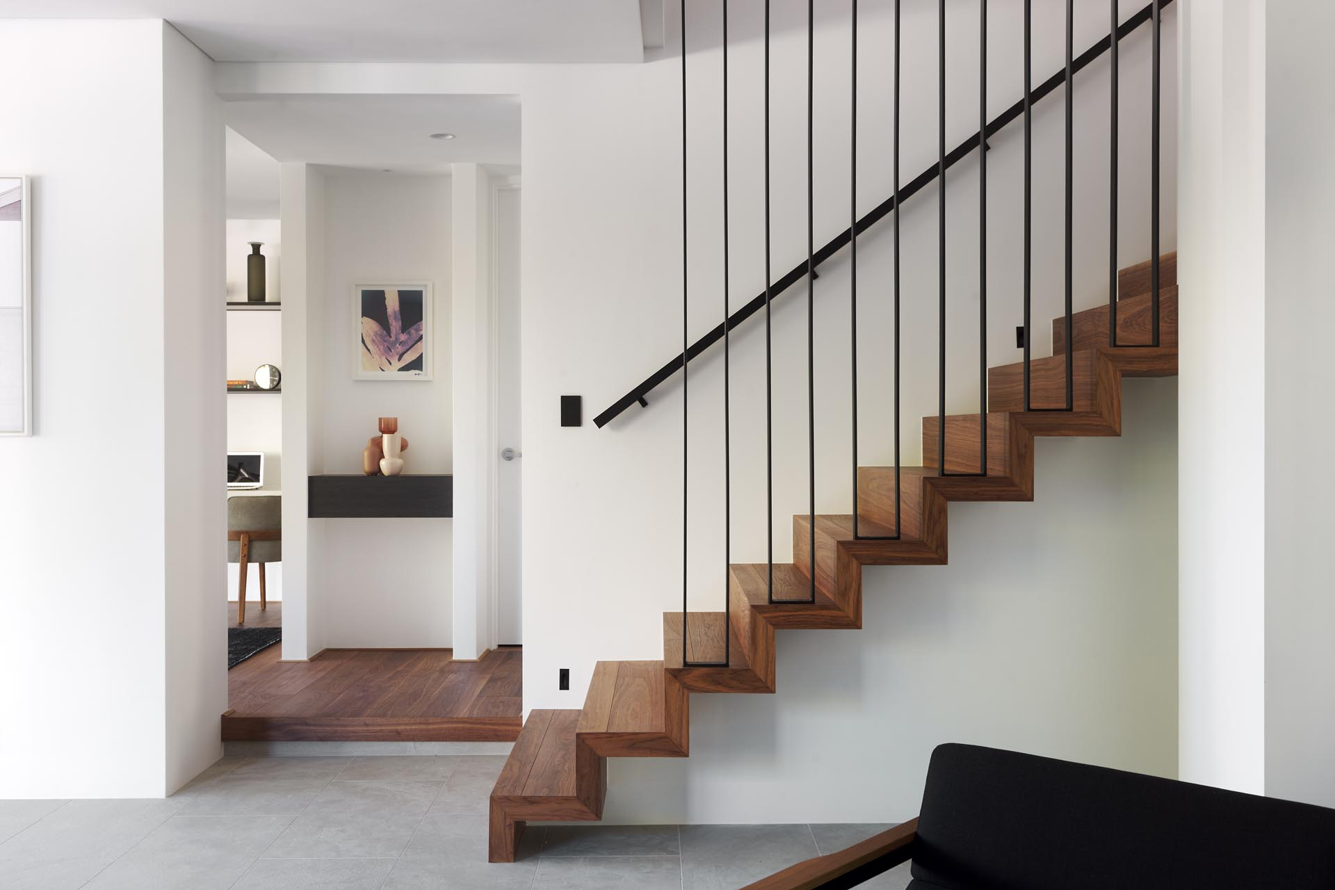 A modern house interior that includes wood stairs with a black metal railing that lead to the upper floor of the home.