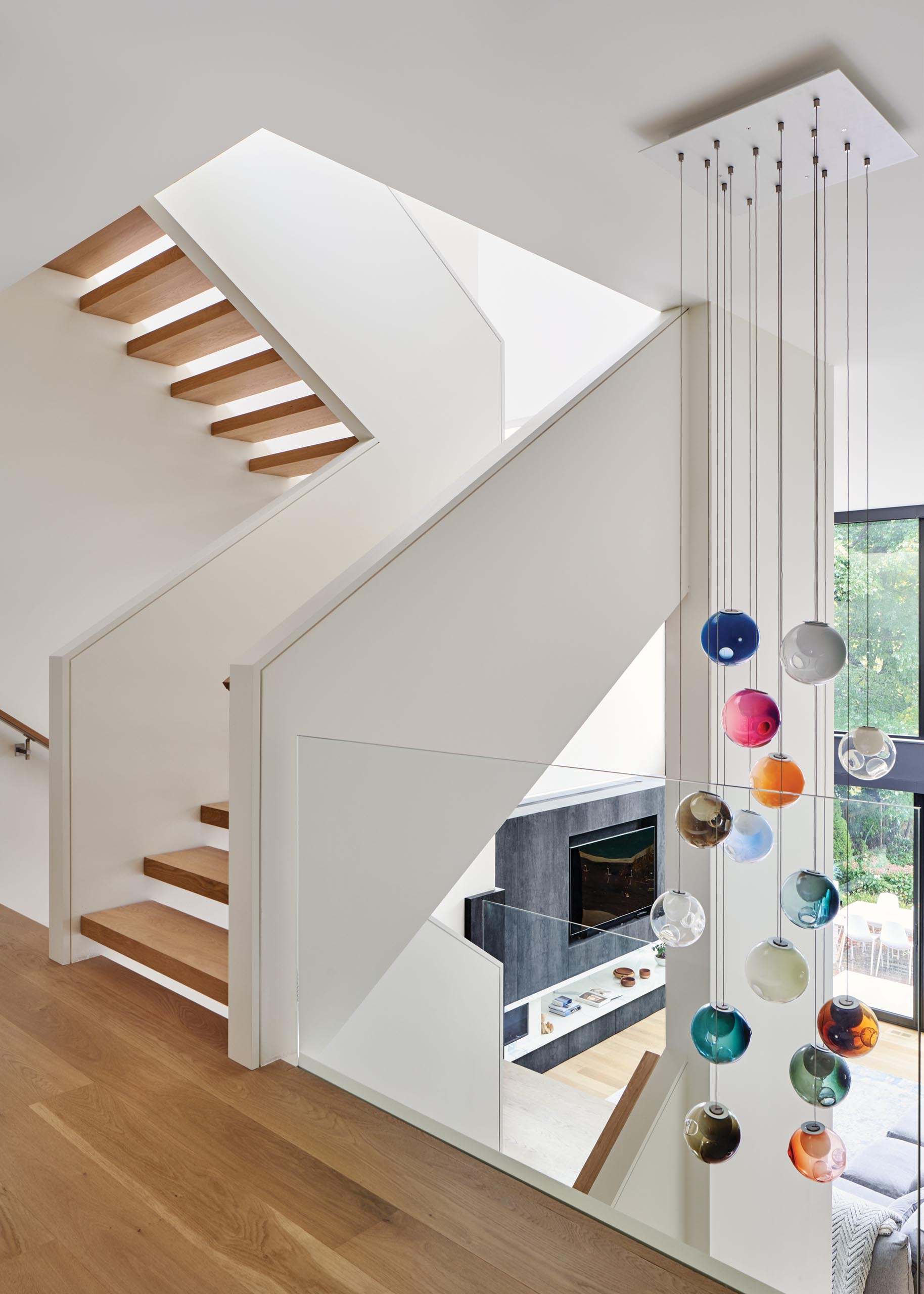 A modern house with an open wood staircase that has glass railings that connect the multiple levels of the home. A colorful accent has been added with the inclusion of suspended Bocci lights.