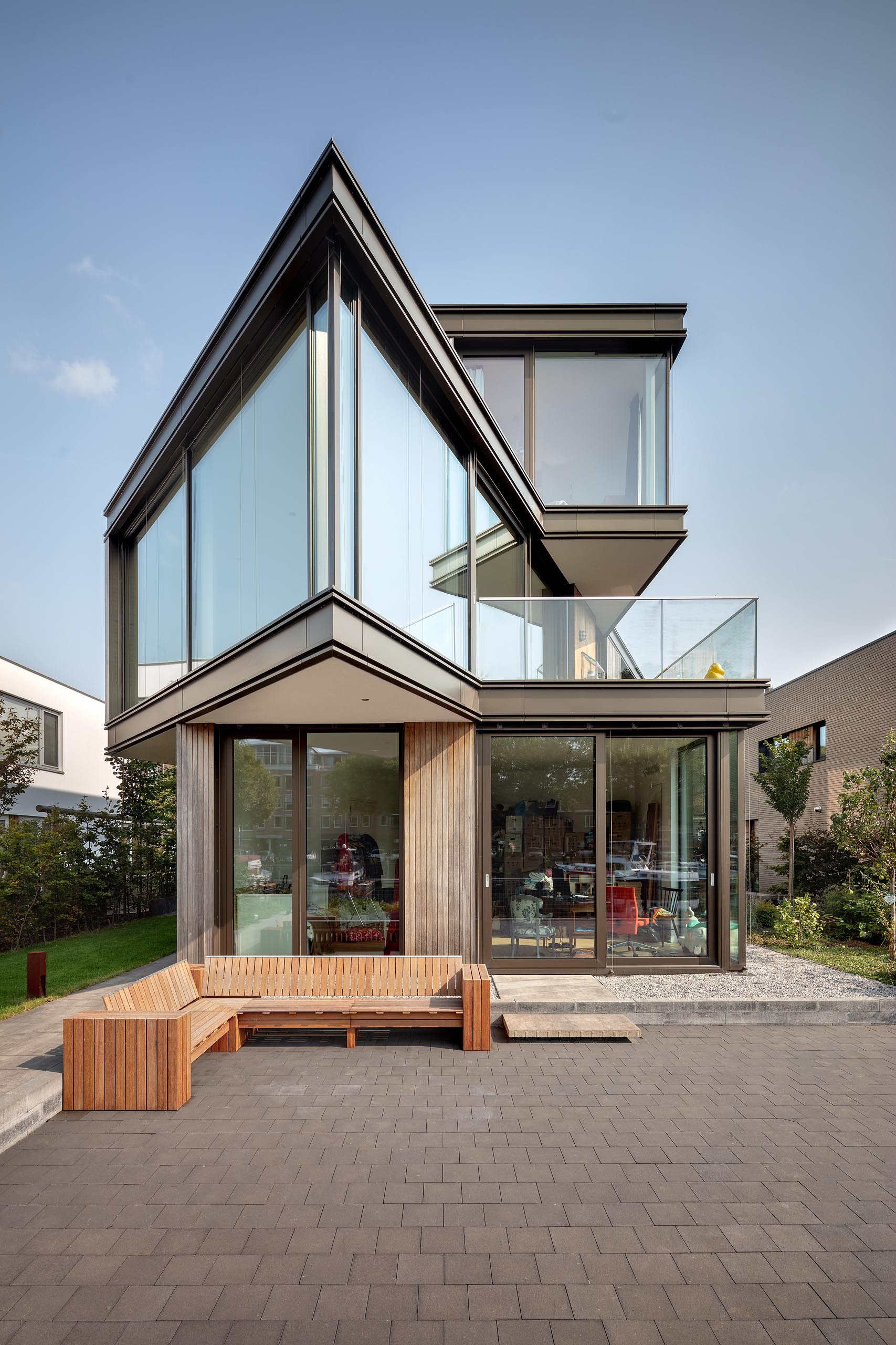 A modern house with a sharp angle and glass walls.