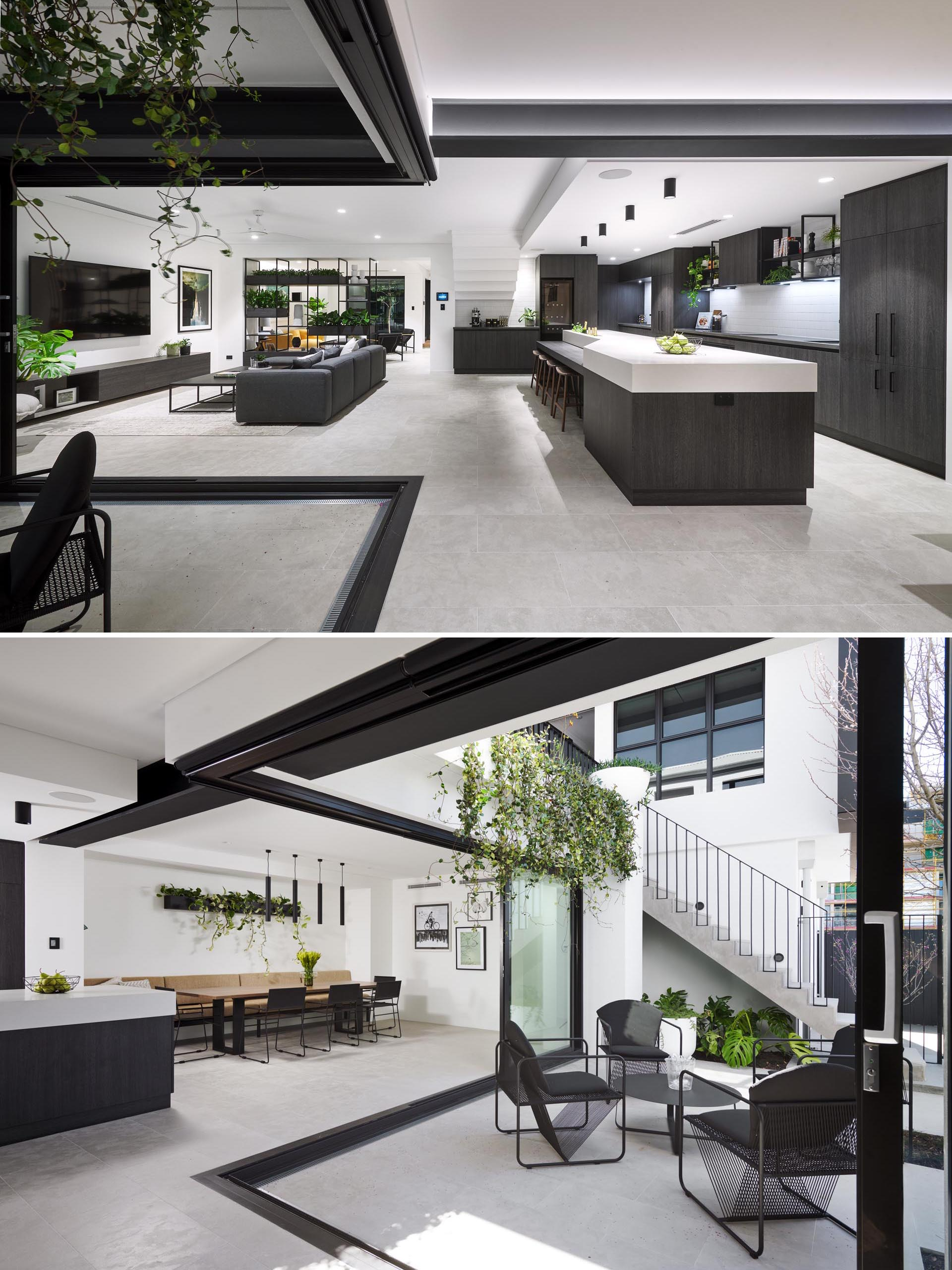 This modern house has retractable glass walls that open the interior spaces to a small outdoor courtyard. The dining room is adjacent to the kitchen and includes a long built-in banquette bench, a wall-mounted planter, and black dining chairs.