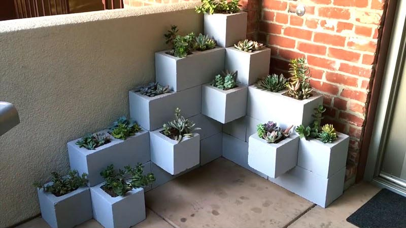 Create your own inexpensive, modern and fully customizable DIY outdoor succulent planter using cinder blocks, landscaping fabric, cactus soil, and succulents.