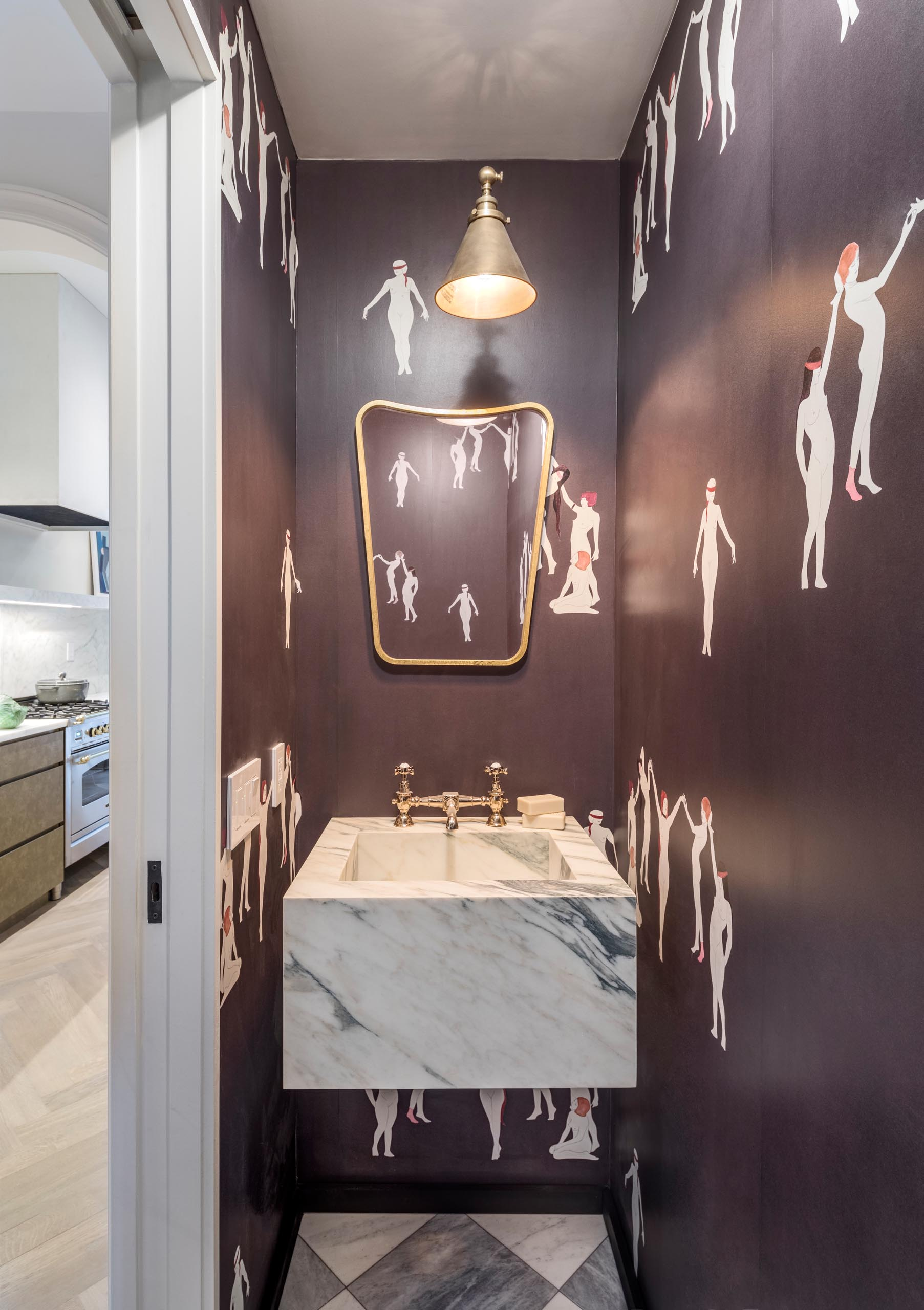 A powder room with gold accents, and black wallpaper that has pictures of women.