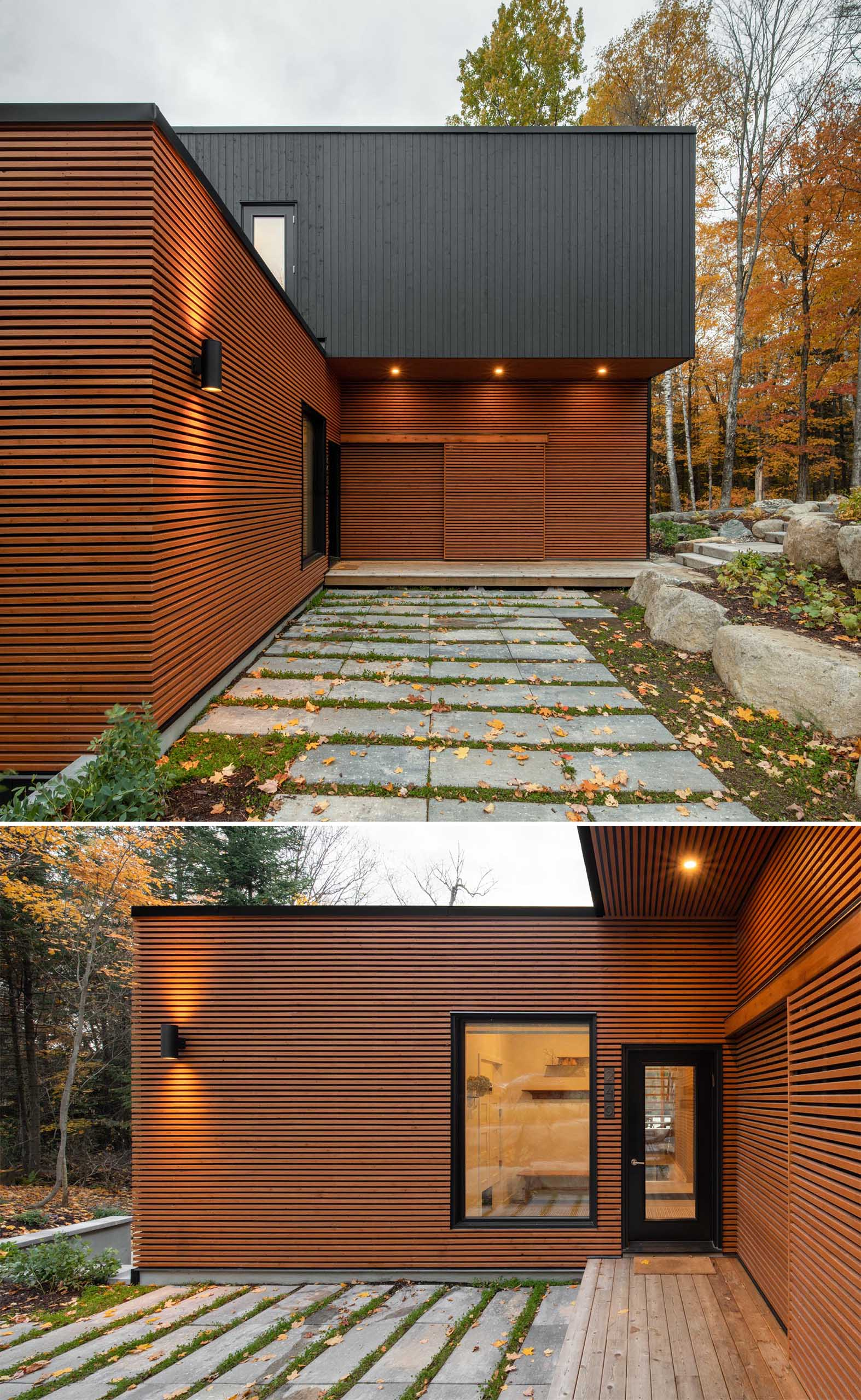 The natural colored exterior of this modern prefab home blends into the wooded area effortlessly, while the opaque black accents add interest.