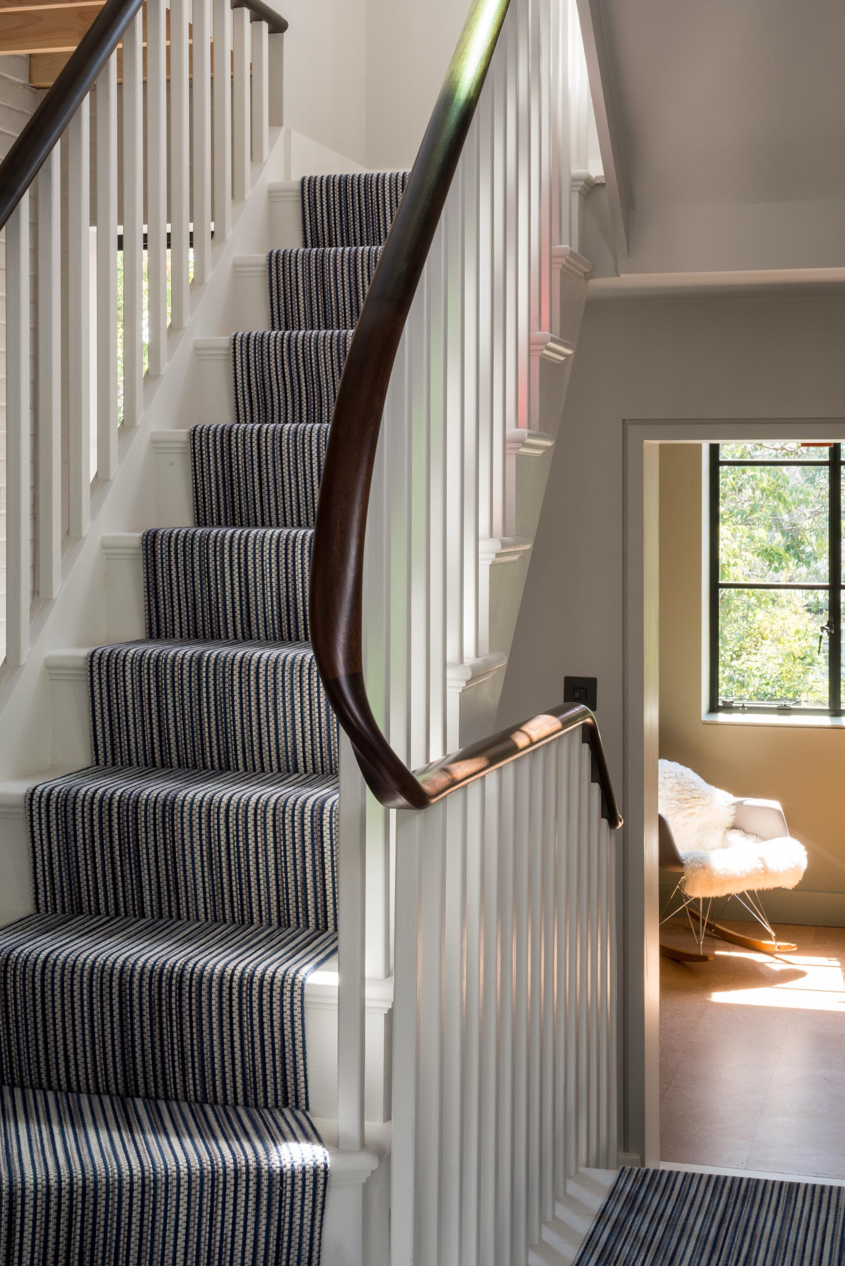 A triple height staircase with white banisters and a curved wood handrail.