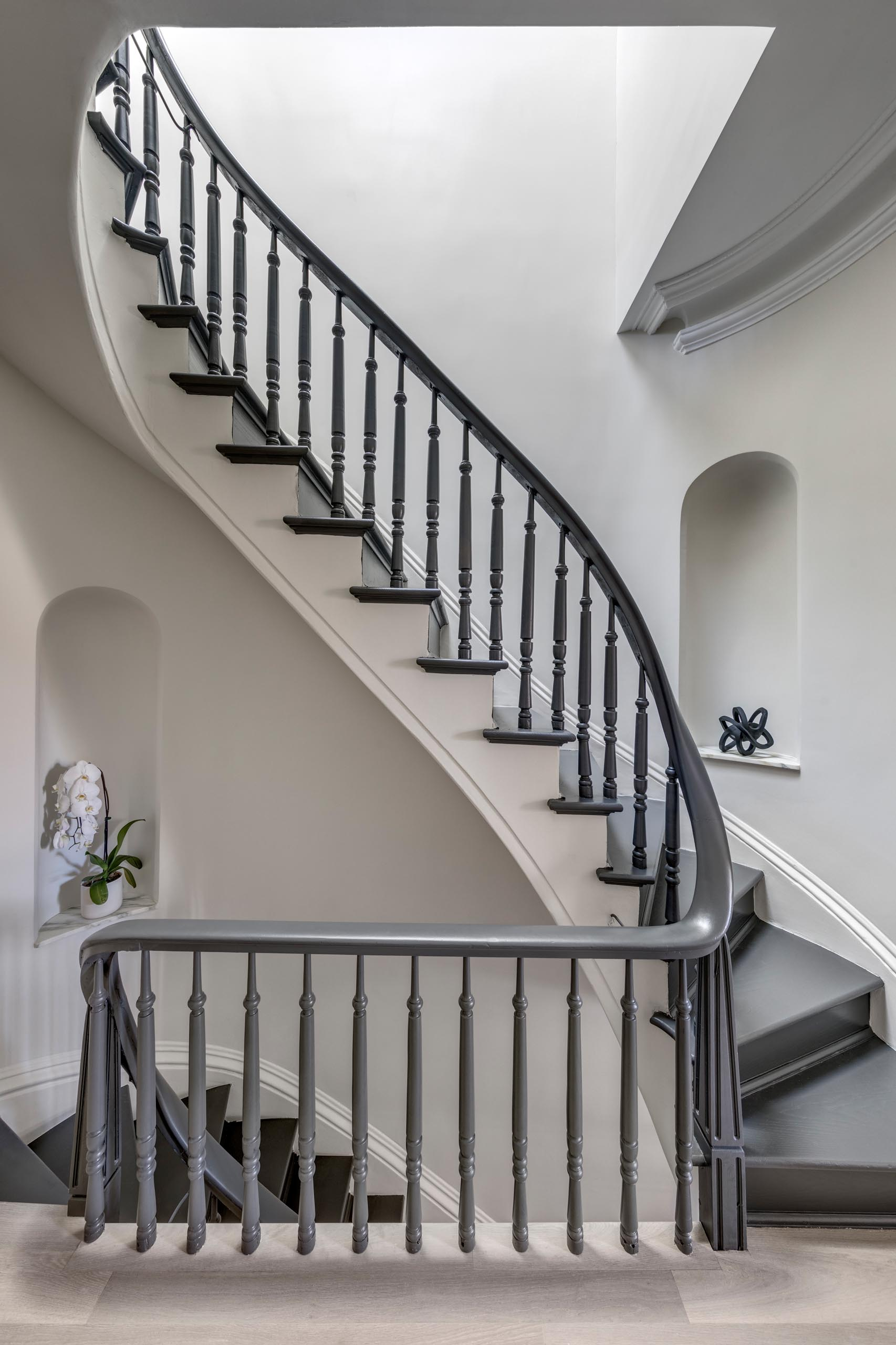 A staircase with a grey handrail and matching stair treads.
