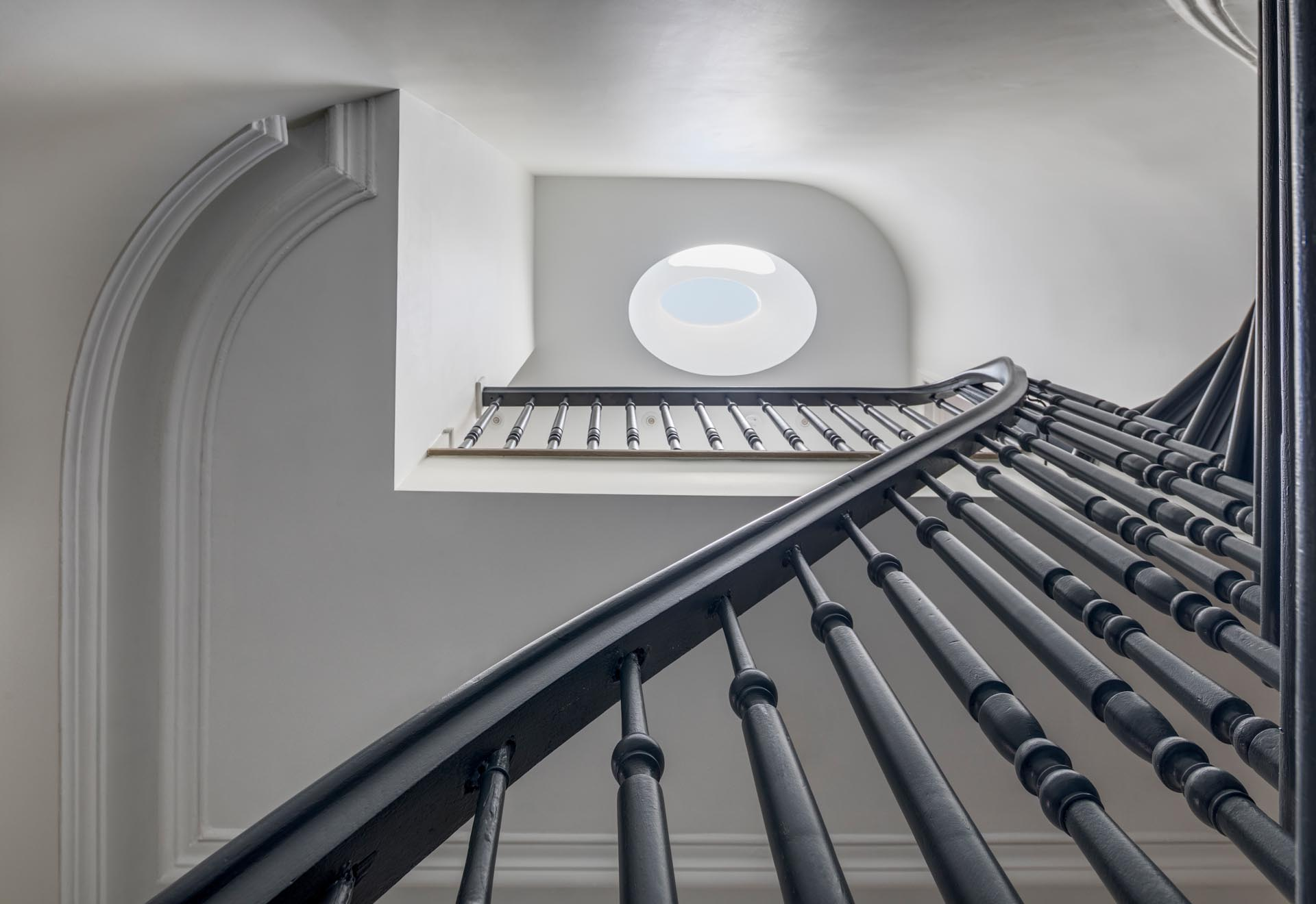 A staircase with a grey handrail and a skylight.