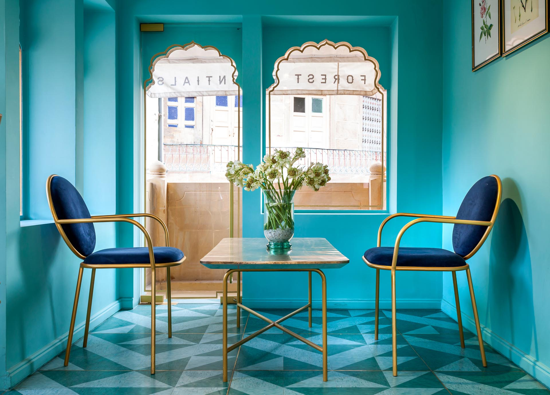 A modern retail store with teal walls, velvet chairs, and gold accents.