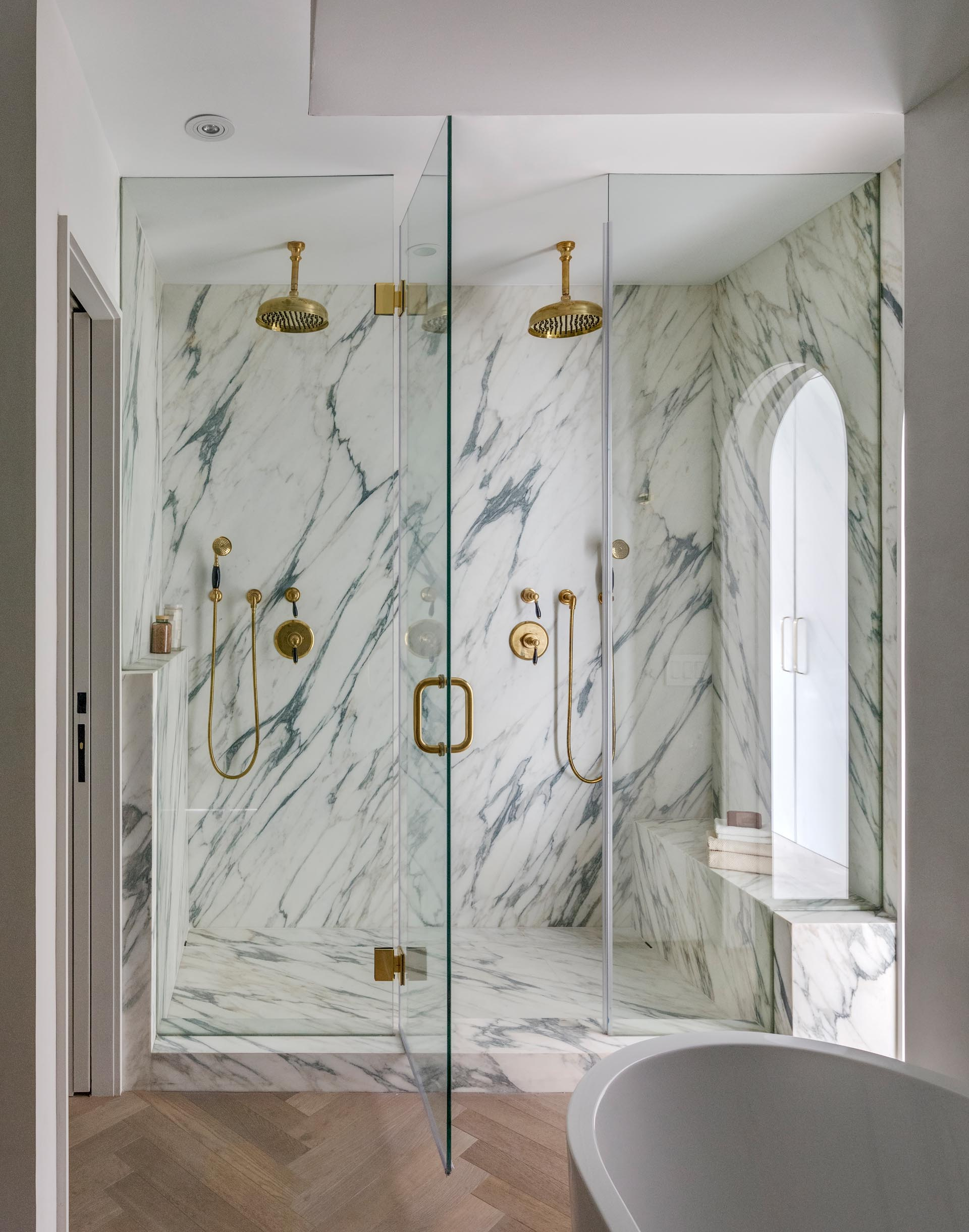 A modern walk-in shower with gold hardware, two shower heads, a glass shower screen and door, and a built-in bench.