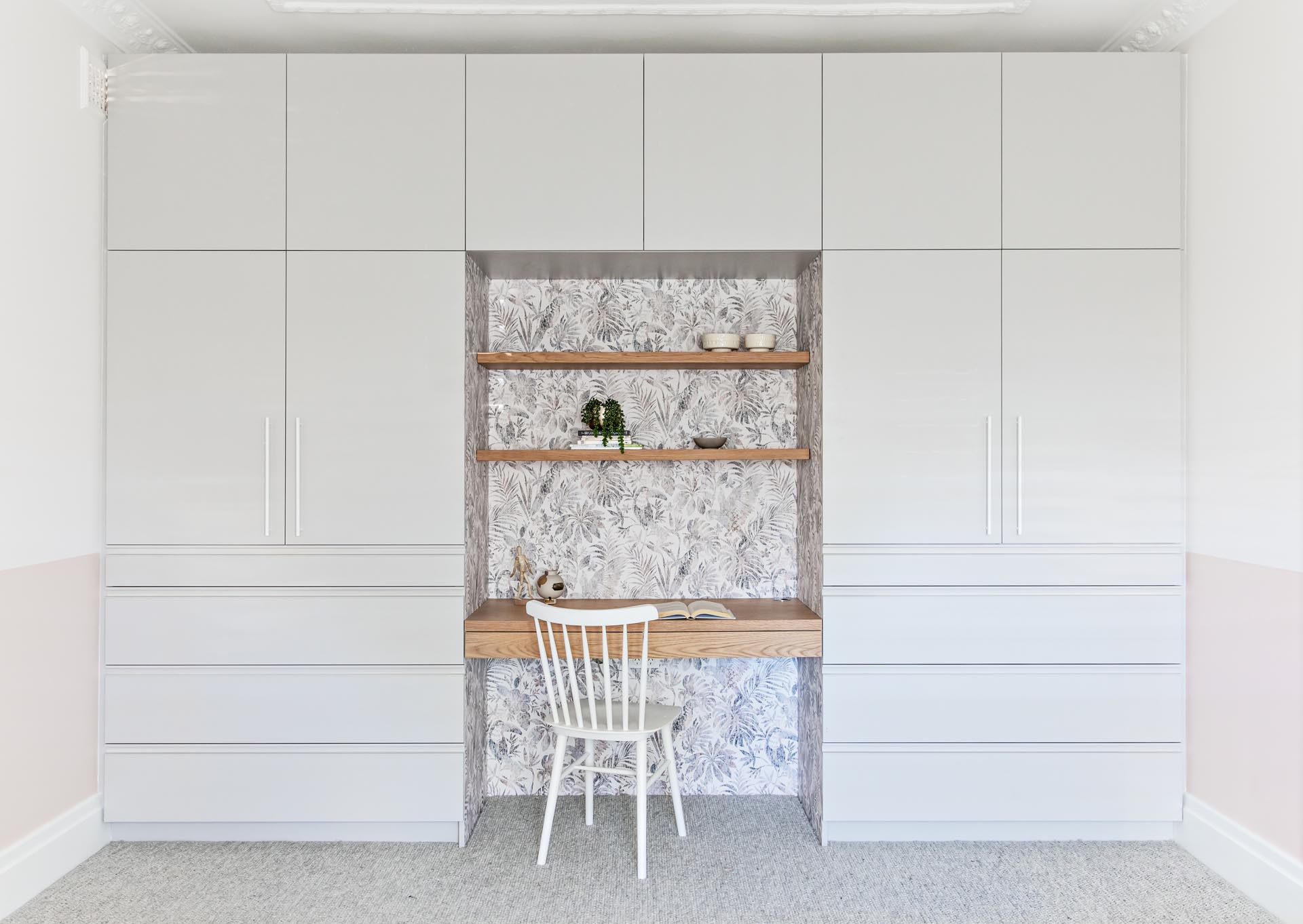 A bedroom with a wall of cabinets and drawers that surround a built-in wood desk and shelving. The desk nook is also lined with a botanical wallpaper.