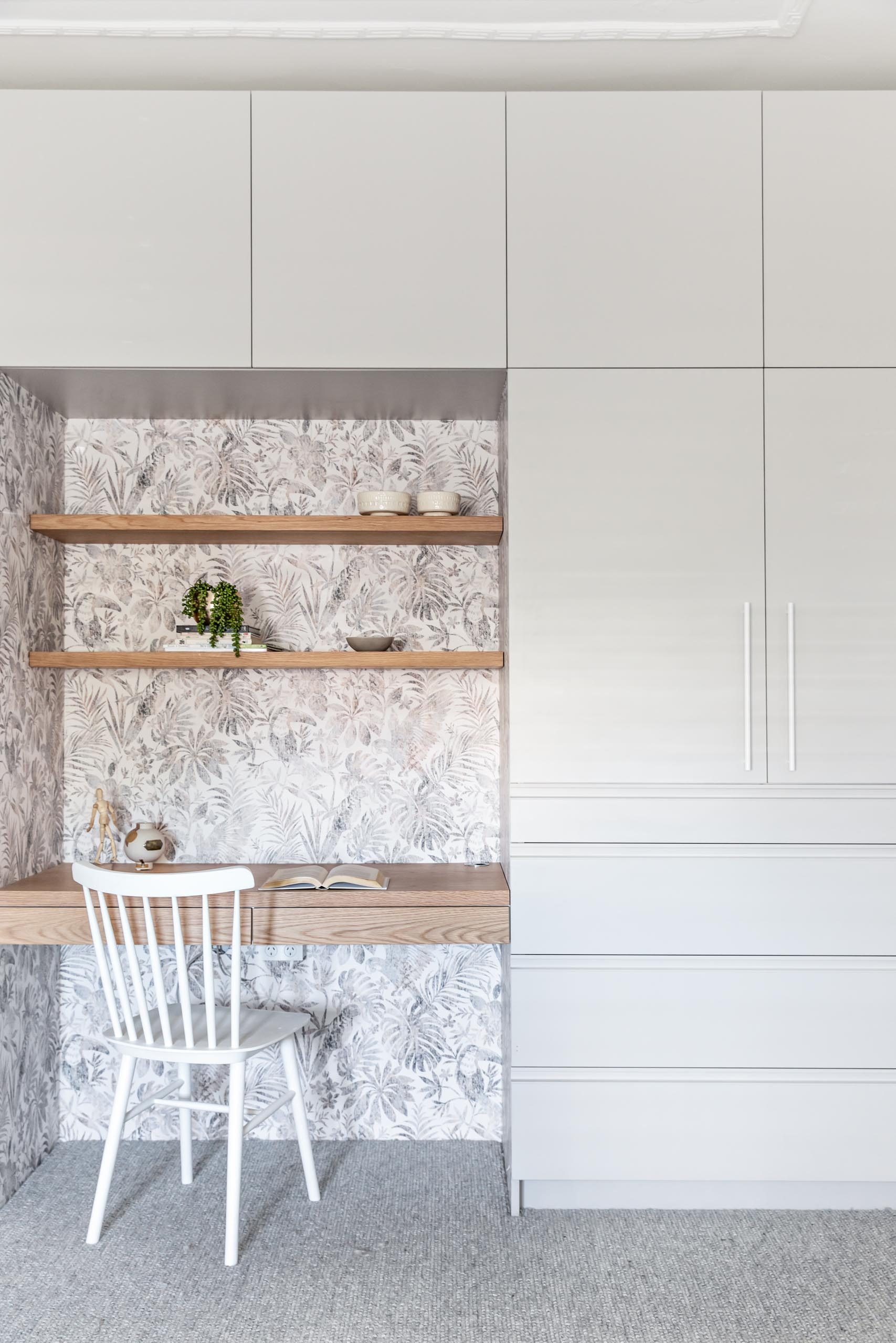 A wall of cabinets and drawers surround a built-in wood desk and shelving. The desk nook is also lined with a botanical wallpaper.