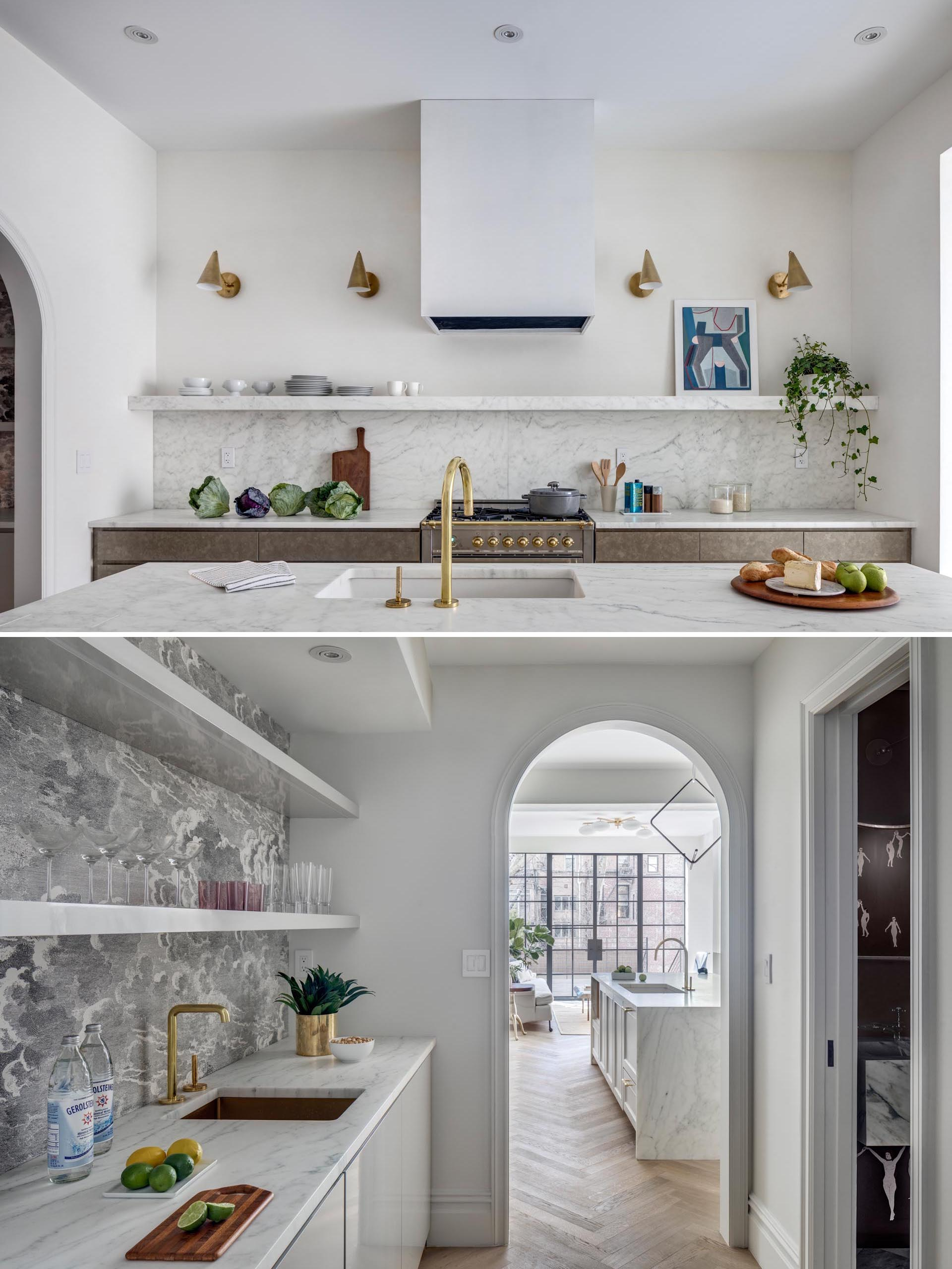 A modern kitchen with marble countertops, an undermount sink, bronze hardware and lighting, and a butler's pantry.