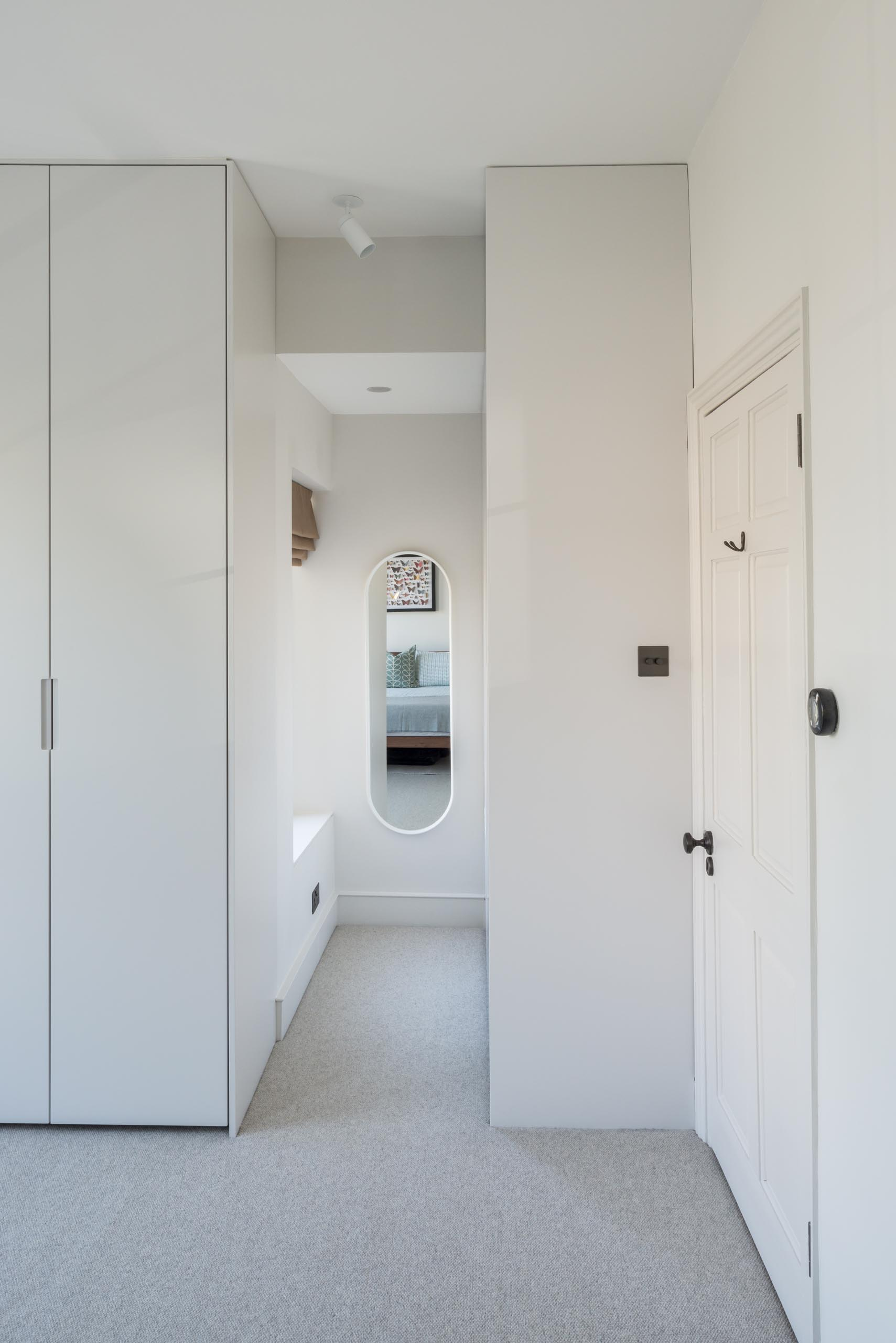 A modern walk-in closet with wood cabinets and a pill-shaped mirror.