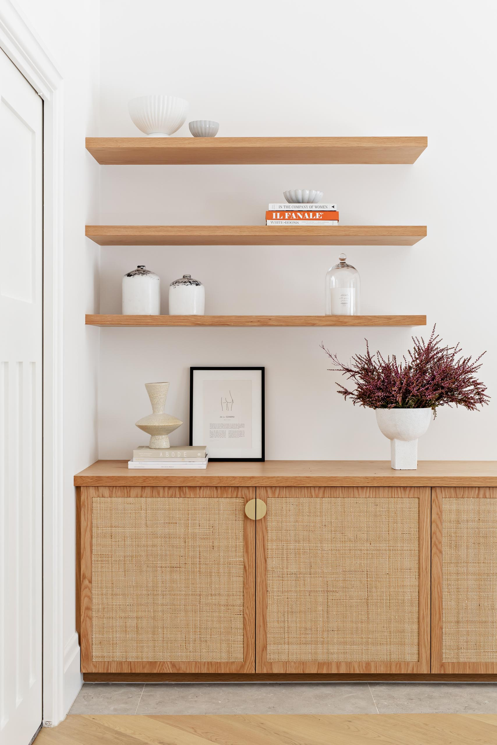 A custom oak and rattan low cabinet, with floating wood shelves above.