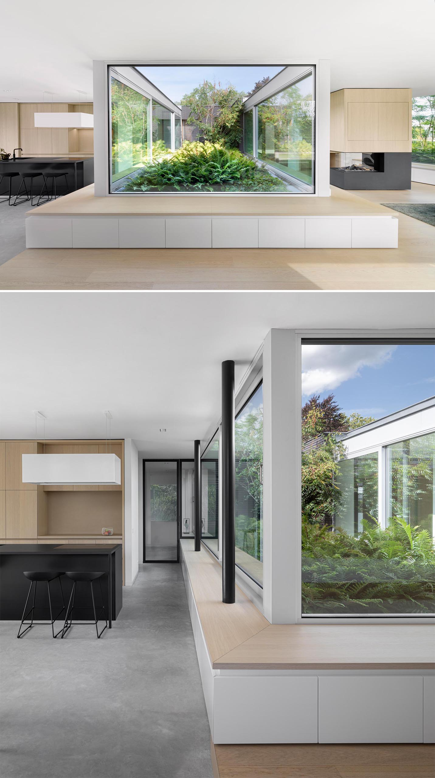 A modern home with a wood bench that  wraps around the windows and provide views of a planted garden.