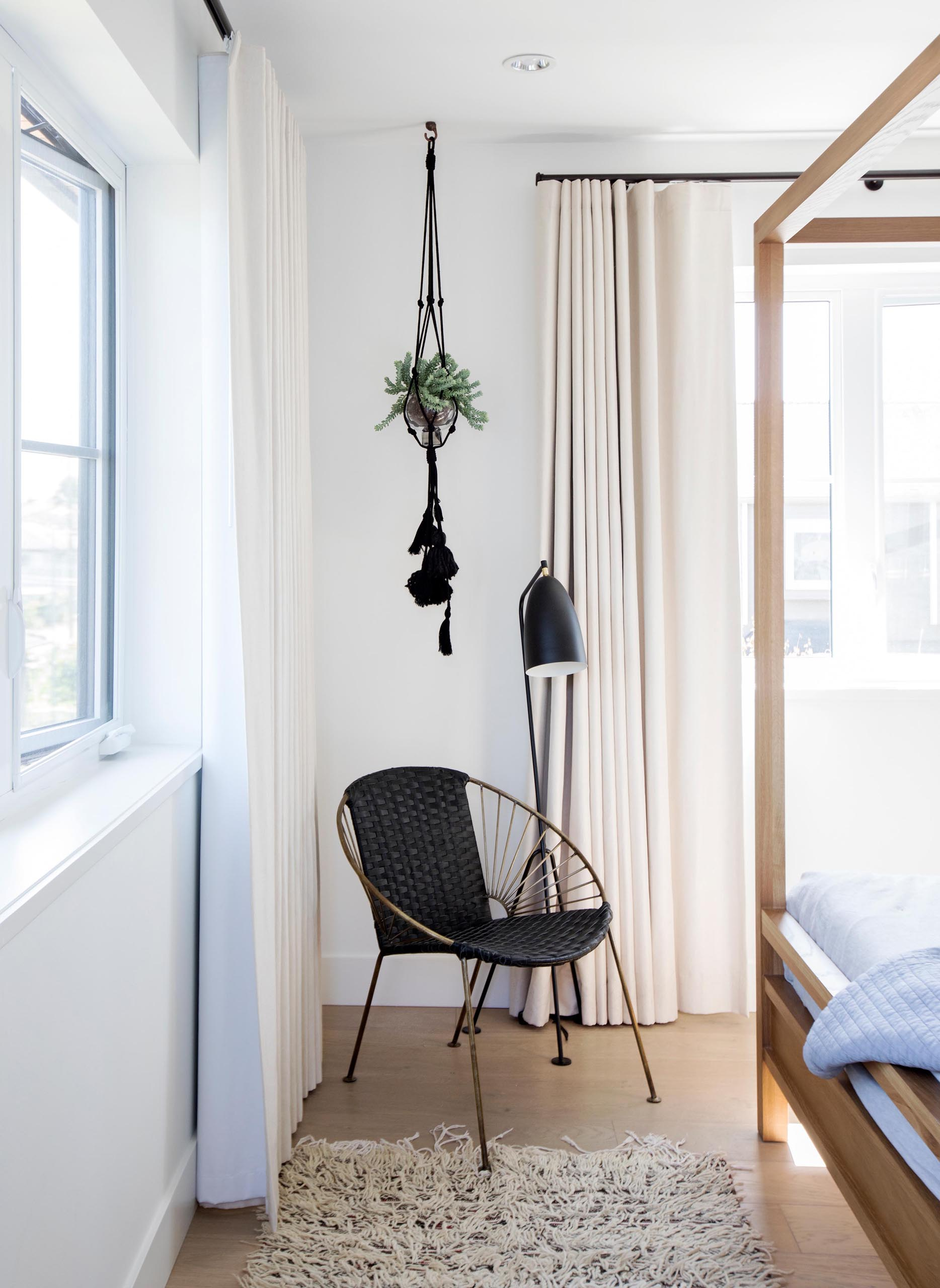 A modern bedroom with a black accent corner furnished with a hanging plant, black floor lamp, and black chair.