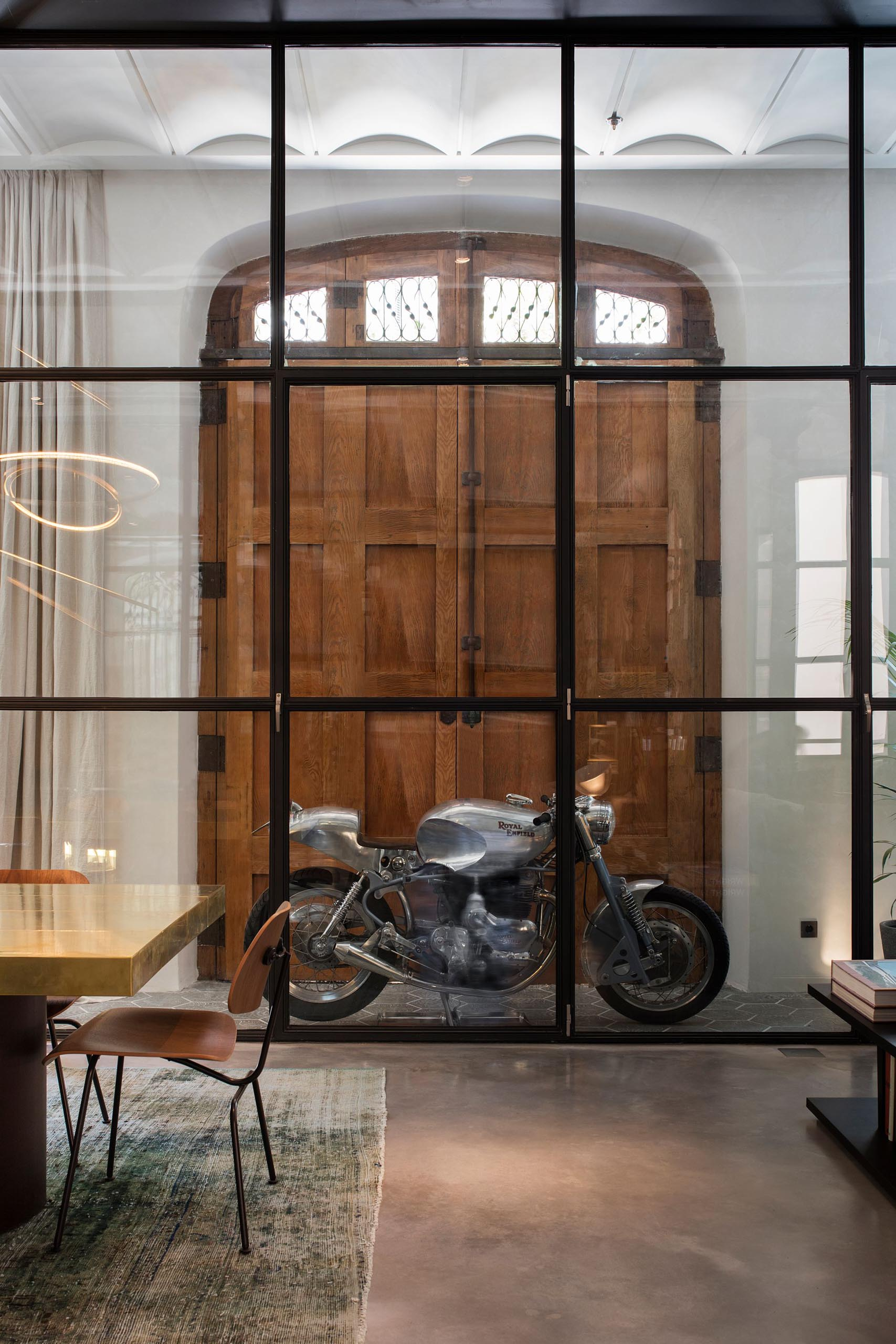 A wall of glass separates the entryway from the open plan interior of this modern apartment.