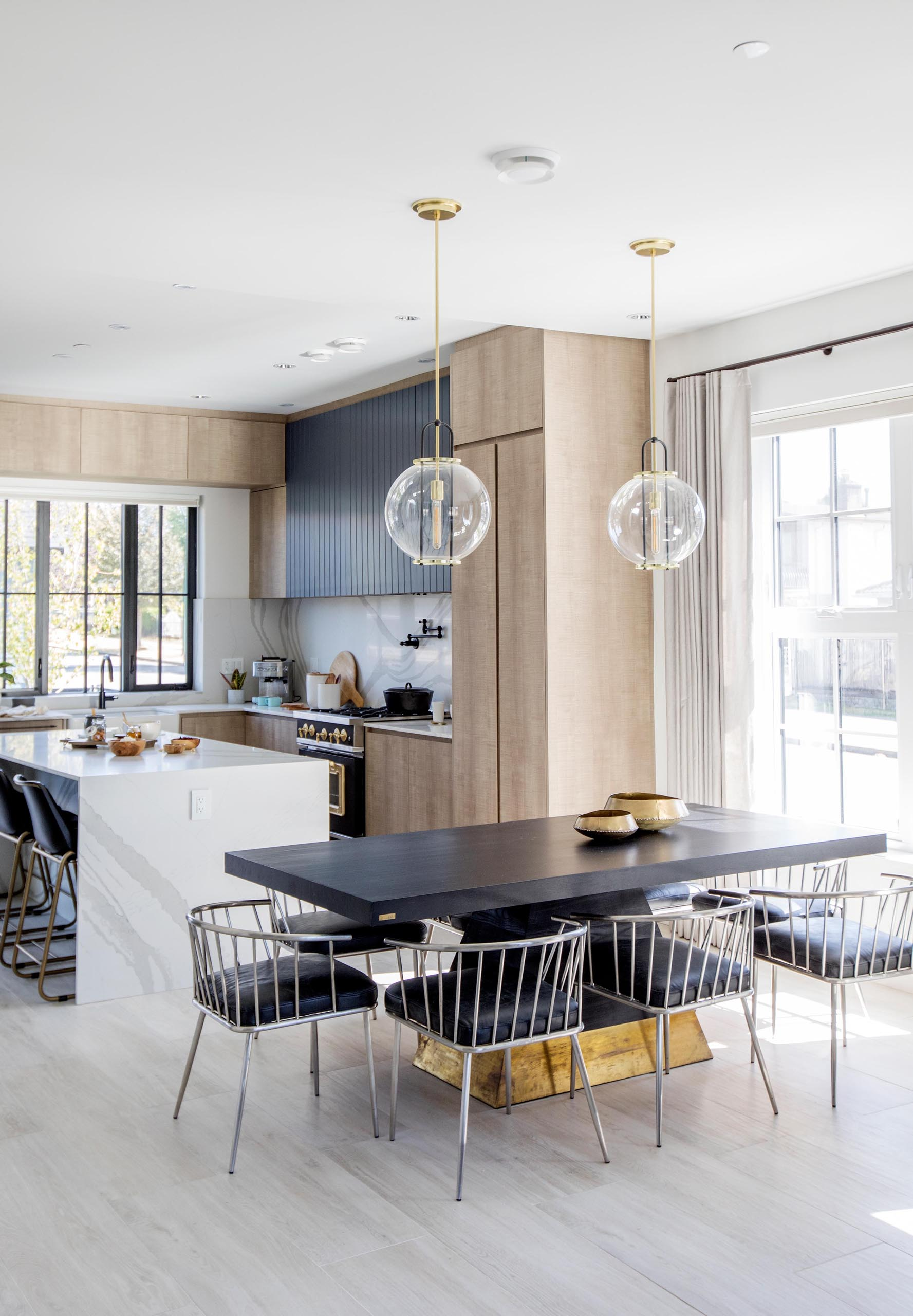A black dining table with gold accents, is anchored in the open floor plan by two glass pendant lights.