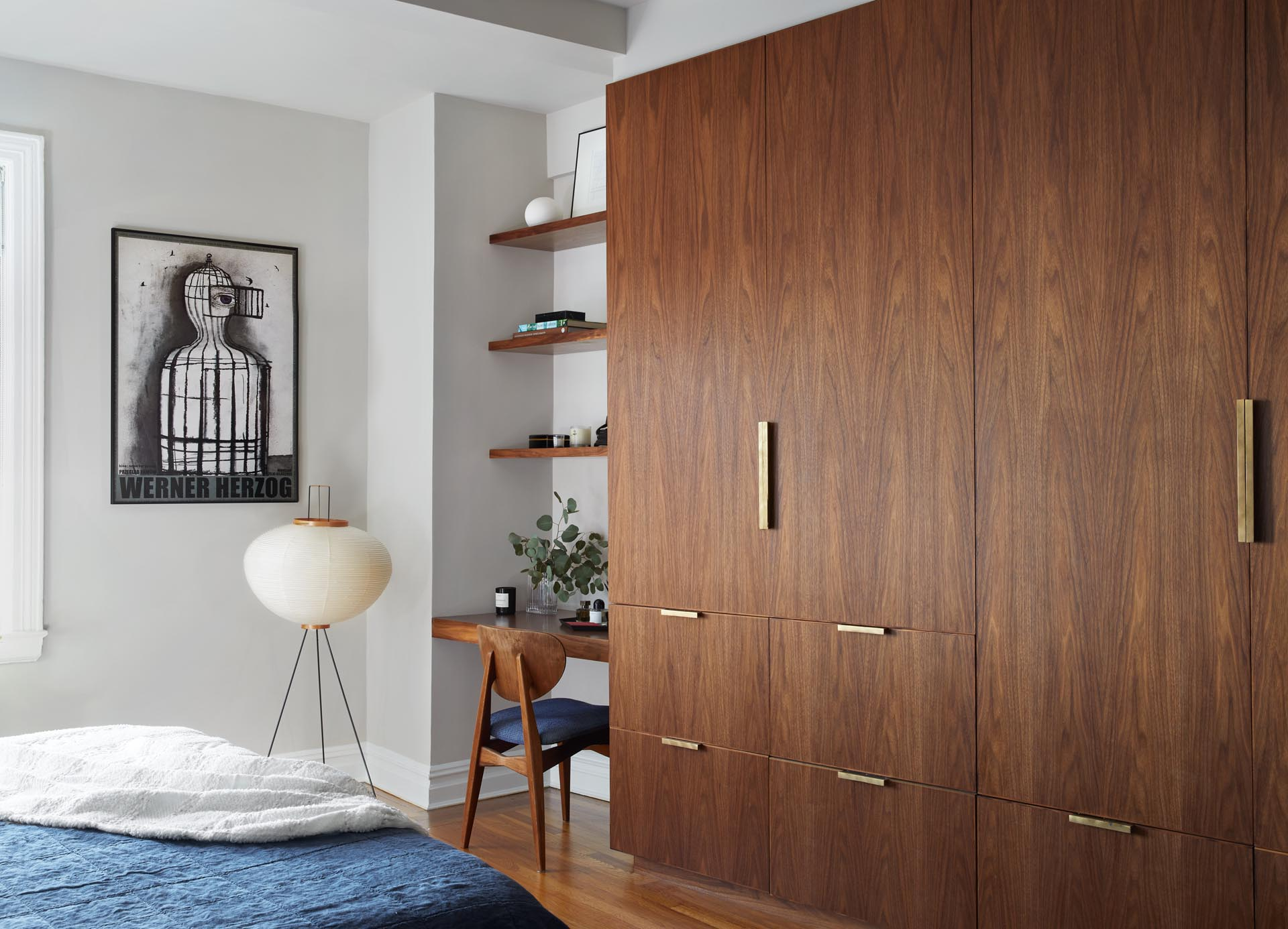 A bedroom with custom walnut wardrobe, storage,and vanity nook (desk), that accented by brass hardware.