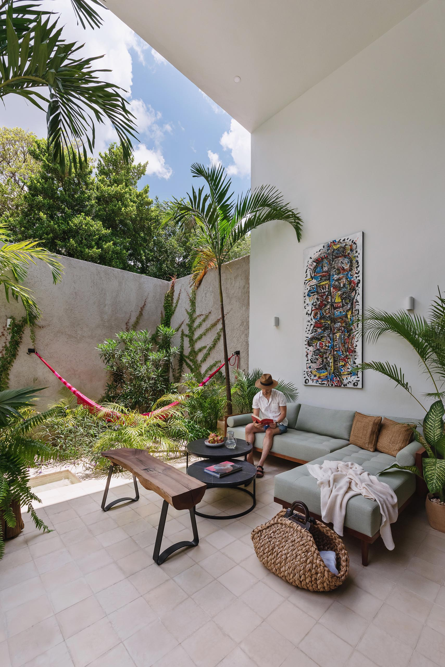 An outdoor living room with a comfortable sofa and a hammock surrounded by tropical plants.