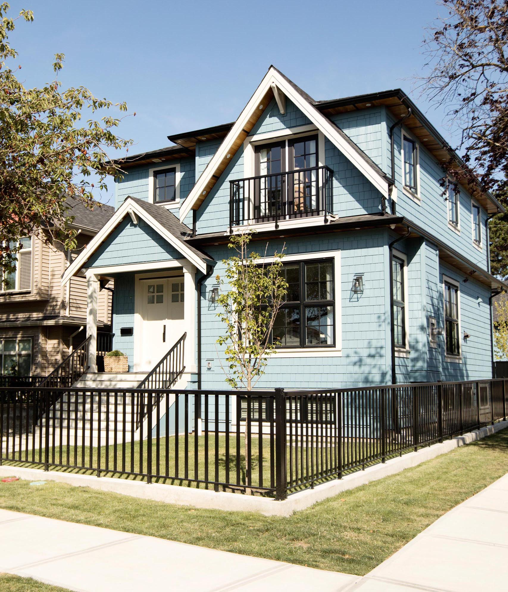 A contemporary light blue house with white trim and contrasting black fence, railings, and window frames.