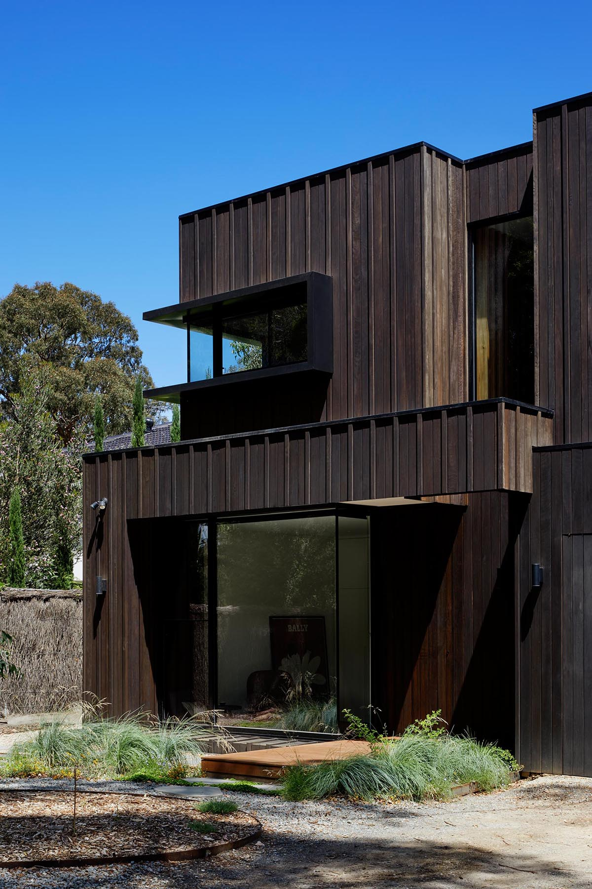 The exterior of this modern home showcases Blackbutt timber cladding that's accented by black metal window frames.