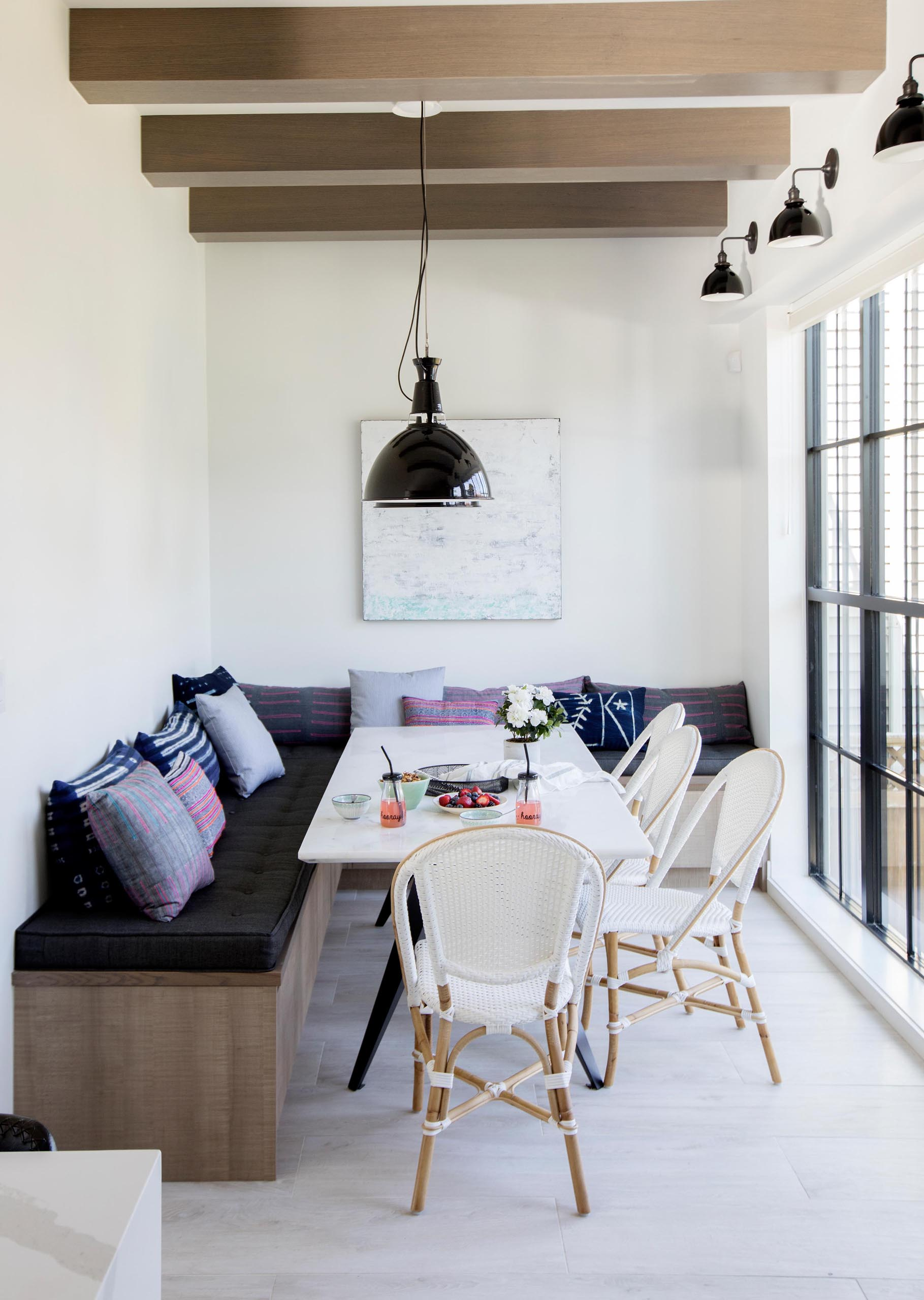 This casual dining area has been furnished with benches and pillows that wrap around the corner of the room.