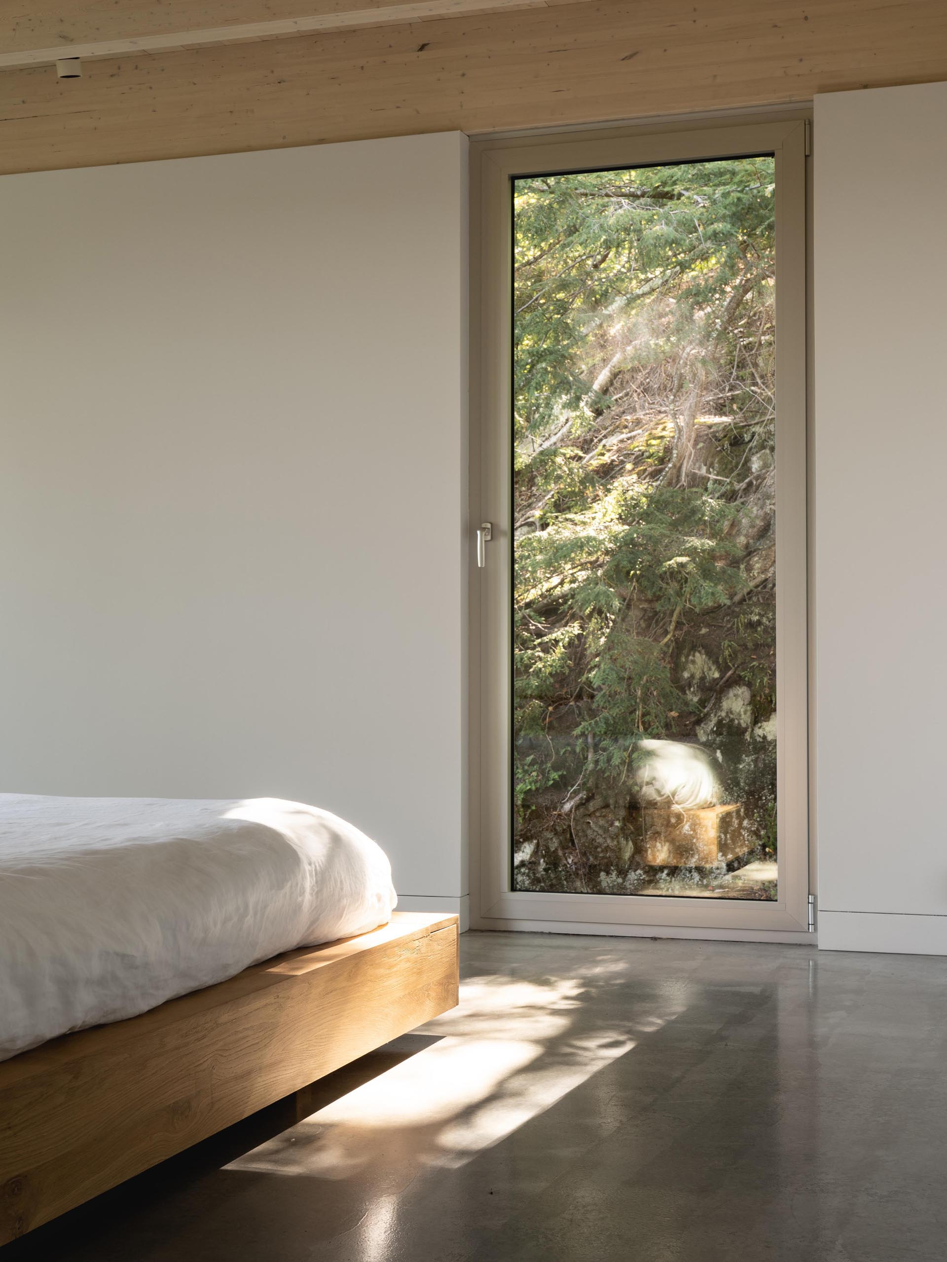 A tall window provides this modern bedroom with views of the forest.
