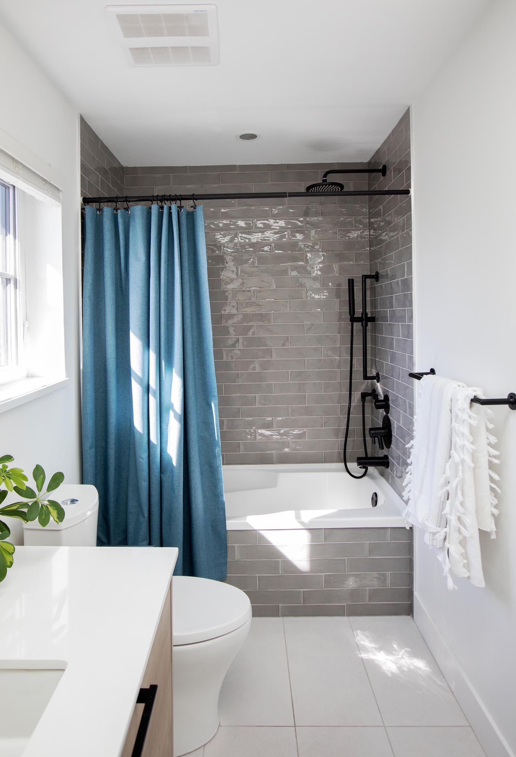 A modern bathroom with a gray-tiled shower, black hardware, and blue shower curtain.