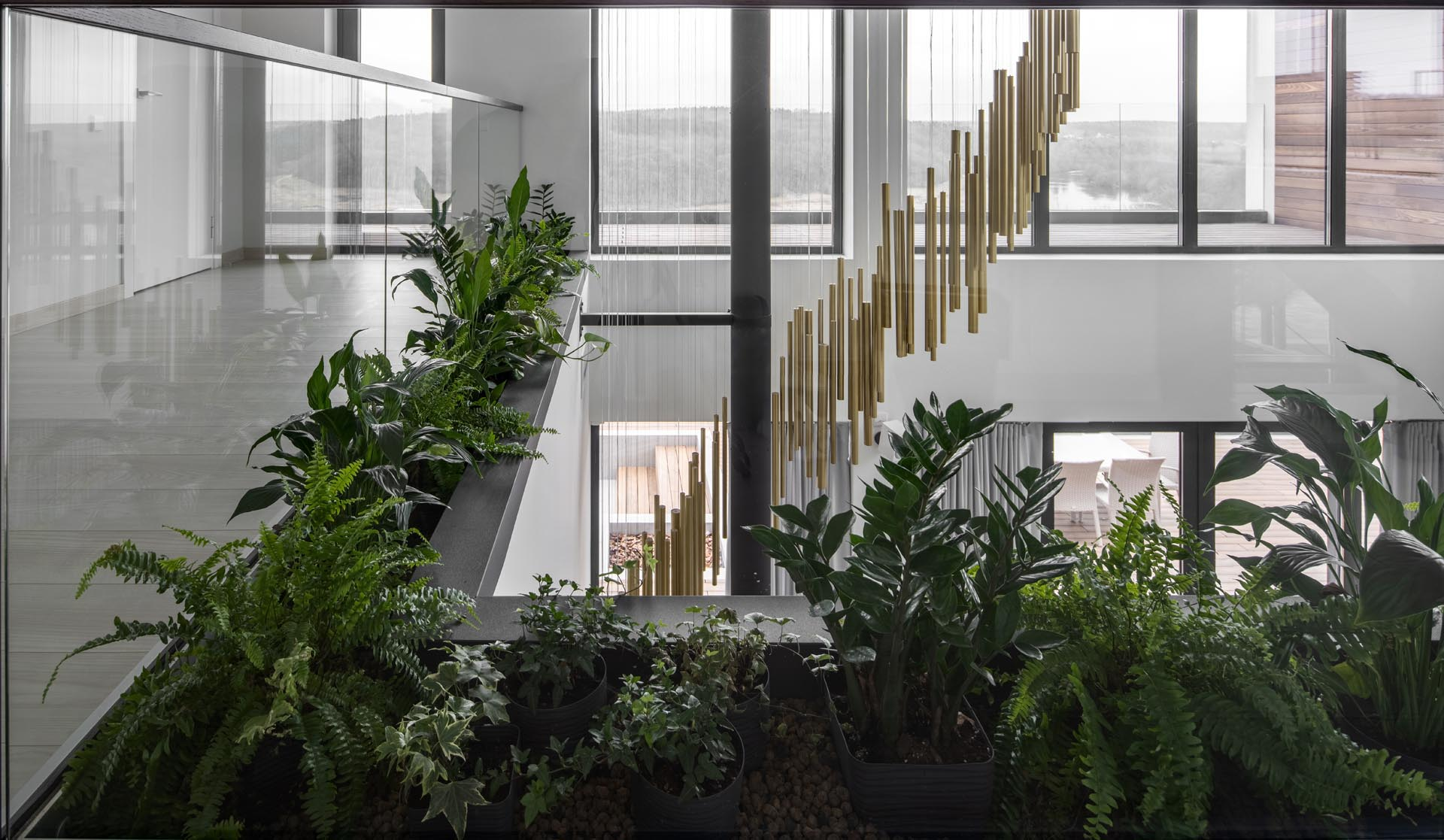 An open walkway with built-in planters and glass railings.
