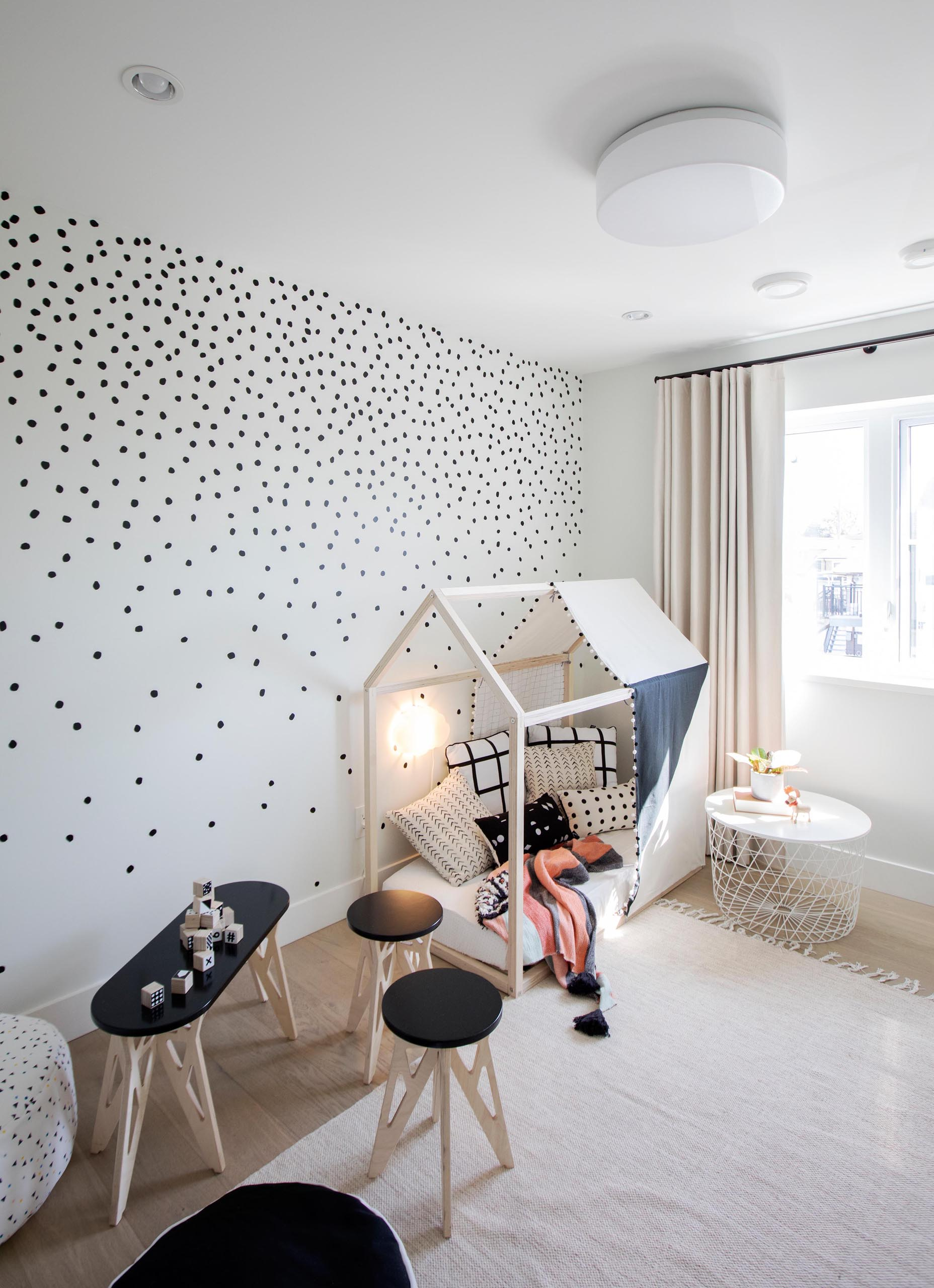 A modern kids bedroom has a playful appearance, with a polka dot pattern on the walls, a small tent, and kid-sized furniture with a table, stools, and poufs.