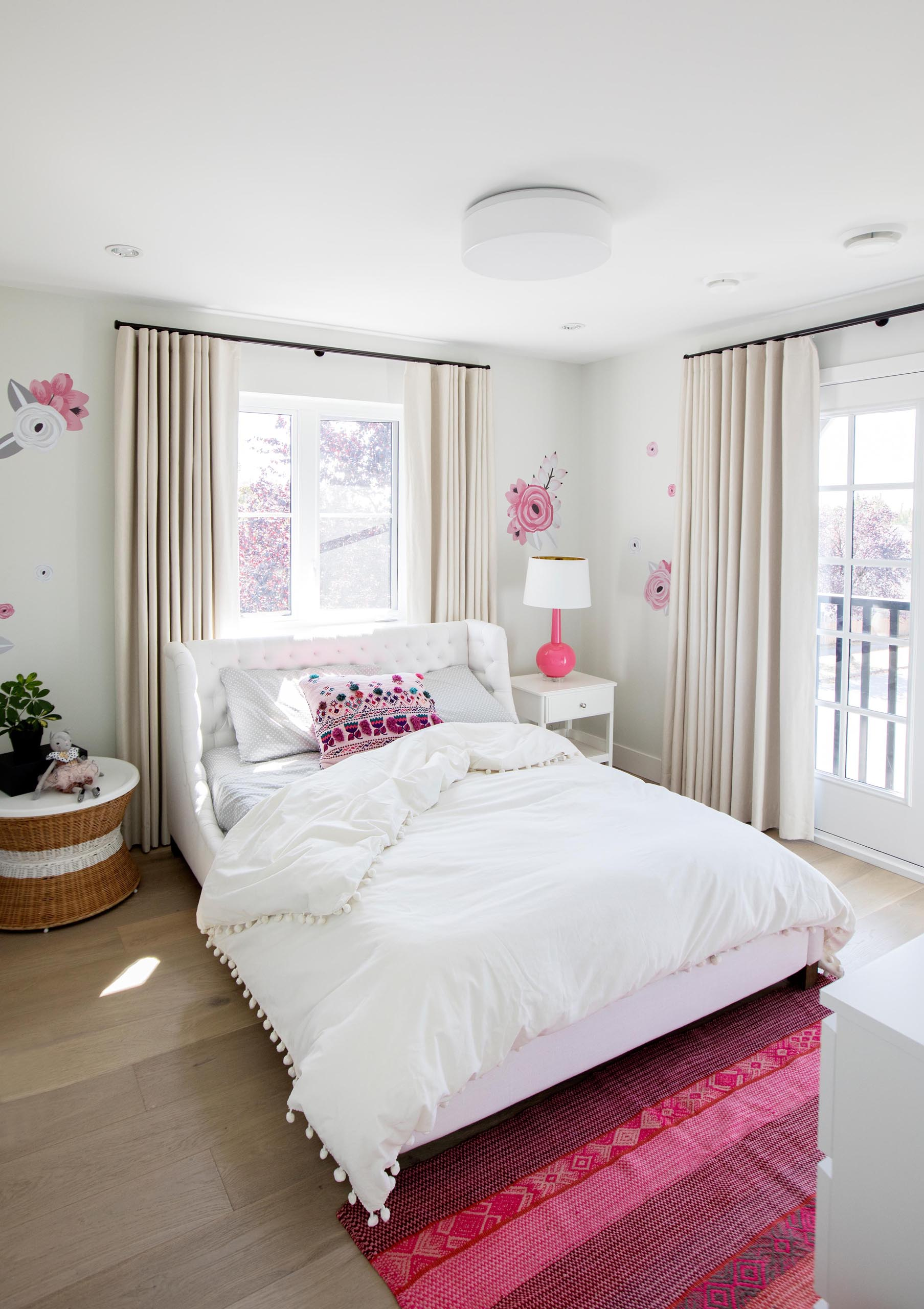 In this bedroom, a pink and white color palette has been chosen. Floral accents adorn the walls, and a striped pink rug is located at the end of the bed,