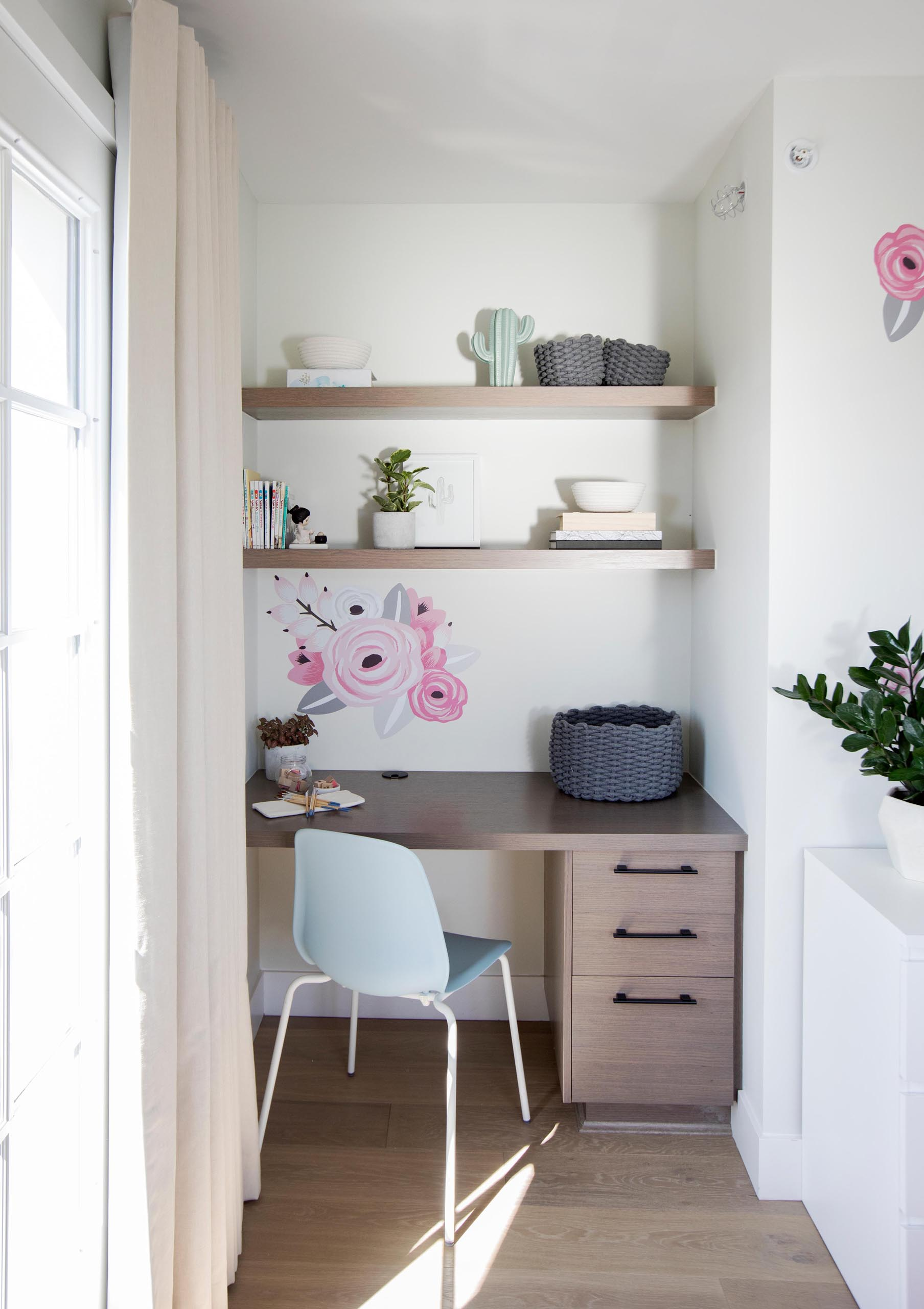 A modern desk with floating shelves has been included in a small alcove in a bedroom.