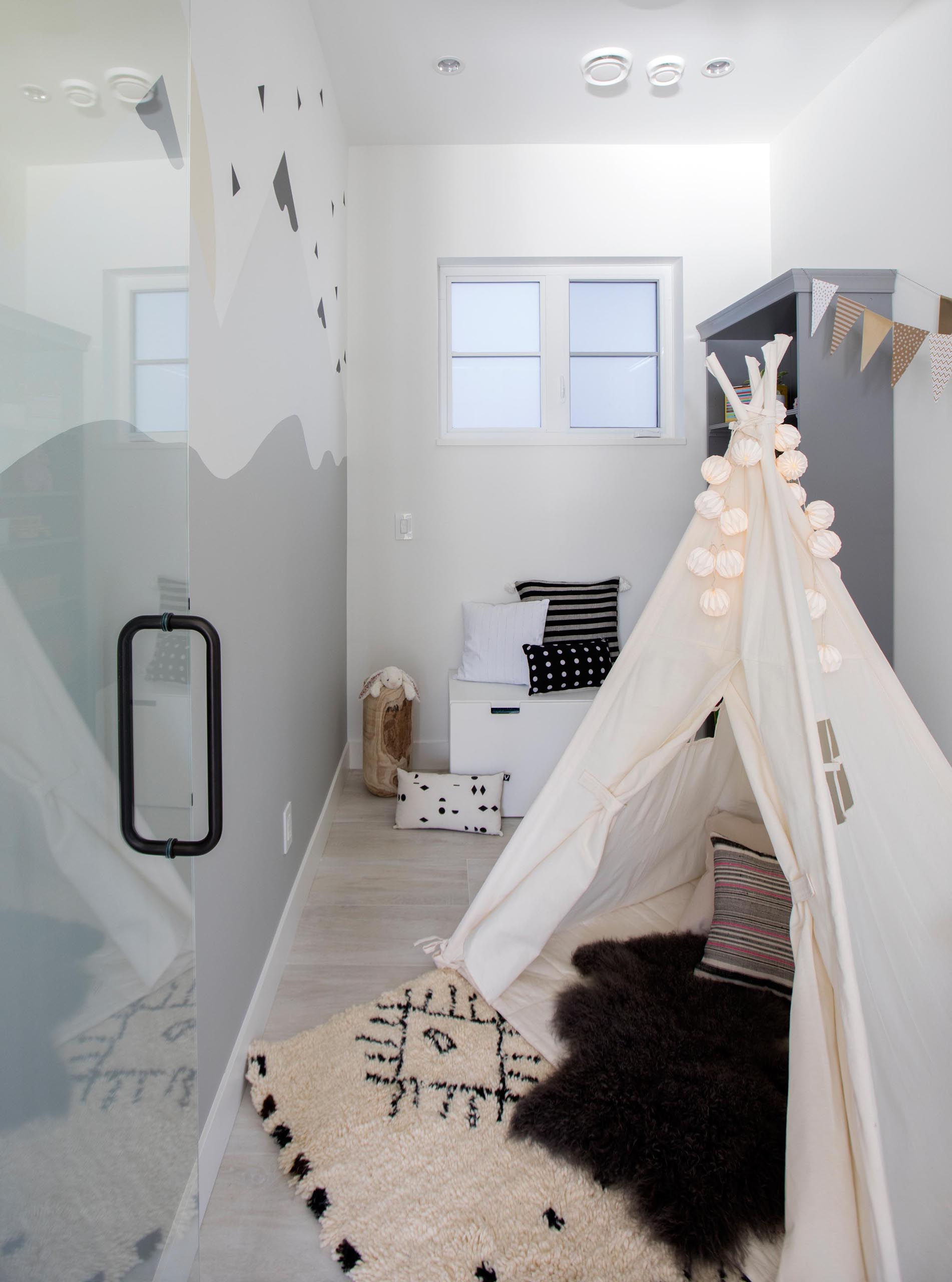 A modern play room with a mountain wall mural, tent, and shelving has been created in a small room.