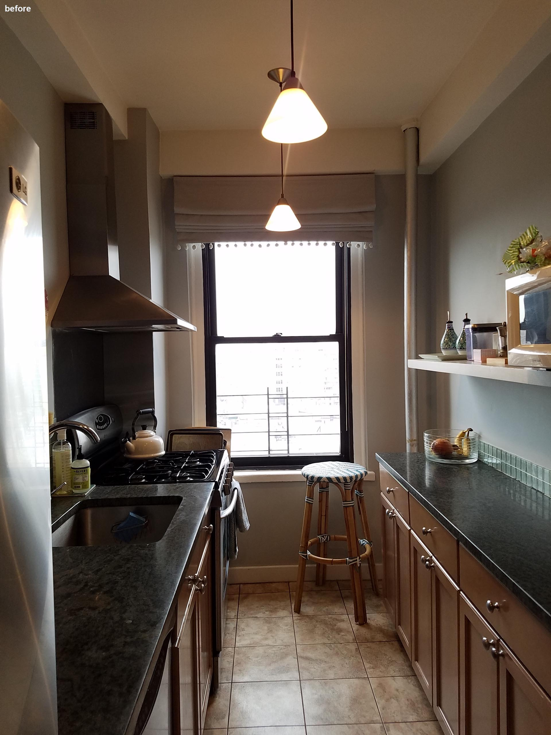 Before photo - a small kitchen with wood cabinets and a dark countertop.