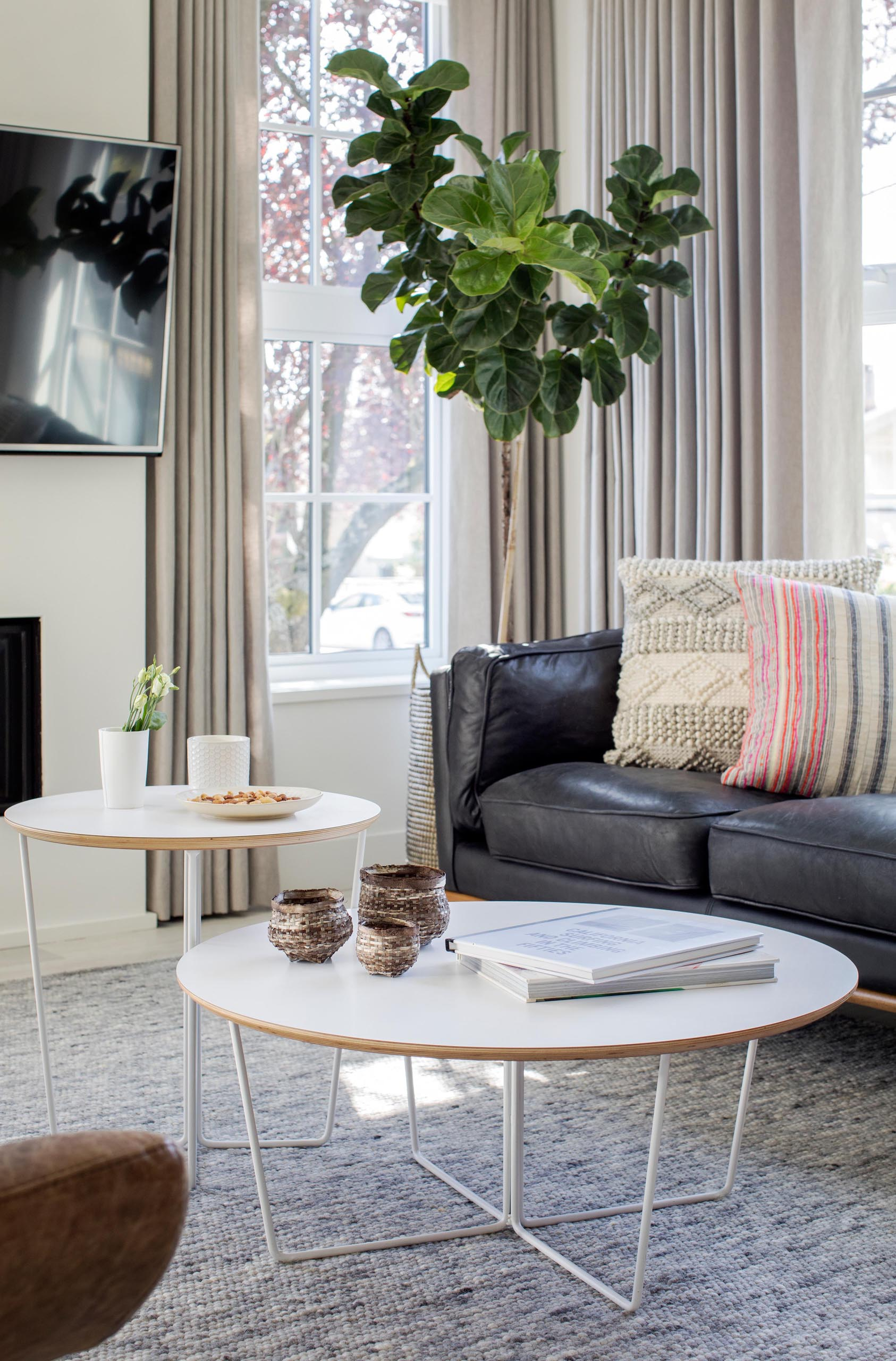 A modern living room with two round white coffee tables.