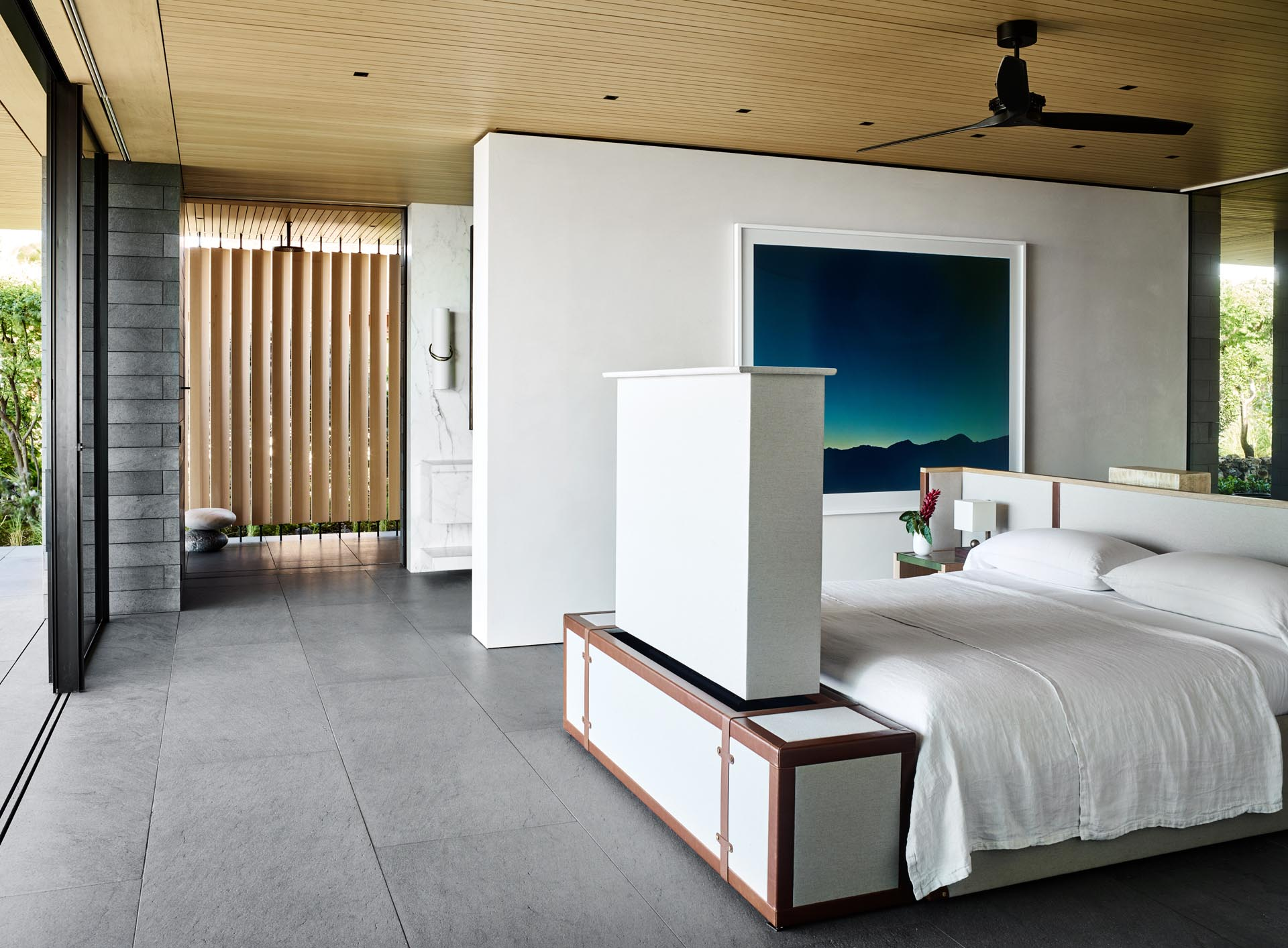 In the master bedroom, the bed frame has been centrally positioned in the room to take advantage of the views. There's also a hidden television at the end of the bed, and behind the headboard, there's a desk.
