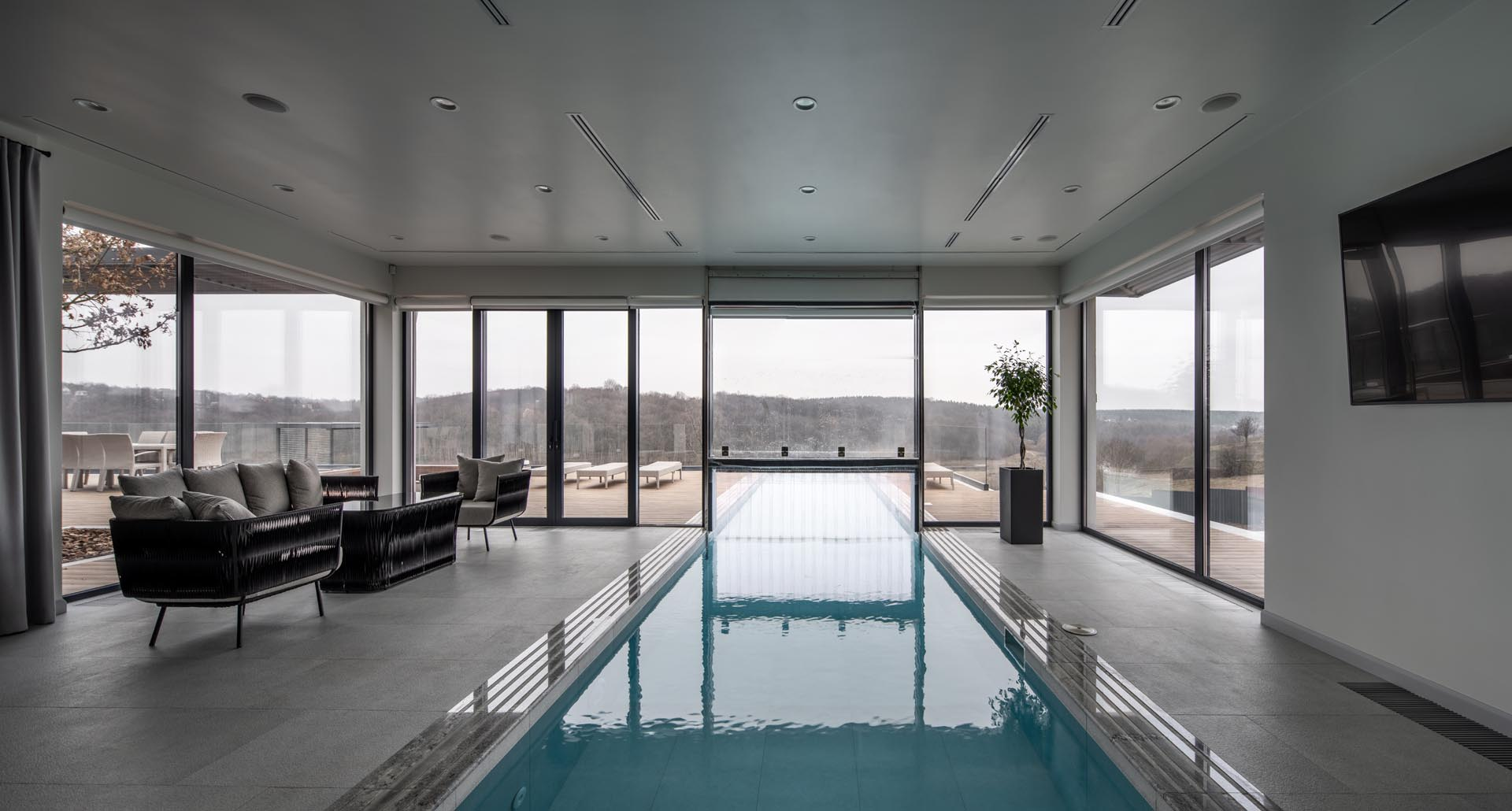 A modern home with an indoor swimming pool that travels through to the outdoors.