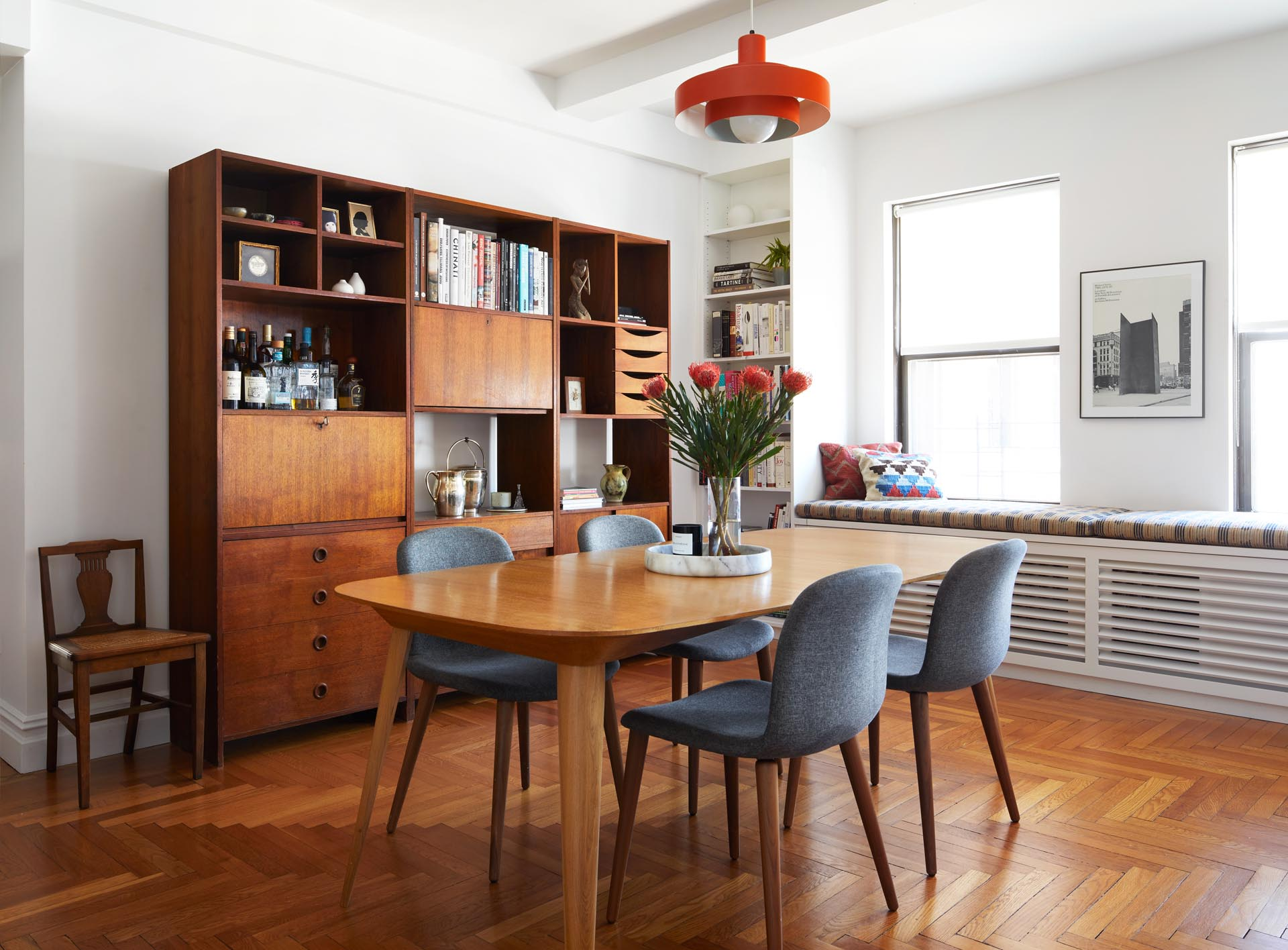 A remodeled dining room includes a deep orange pendant light from the the 1960s, a custom reading bench by the windows, and a vintage Danish media cabinet