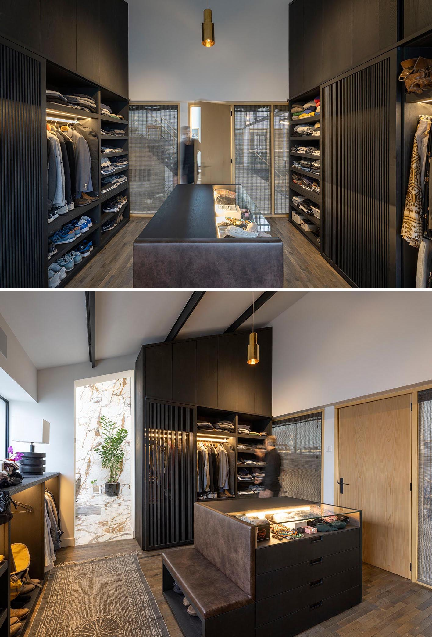 A modern walk-in closet with black cabinets, a central accessories island, and plenty of open shelving.