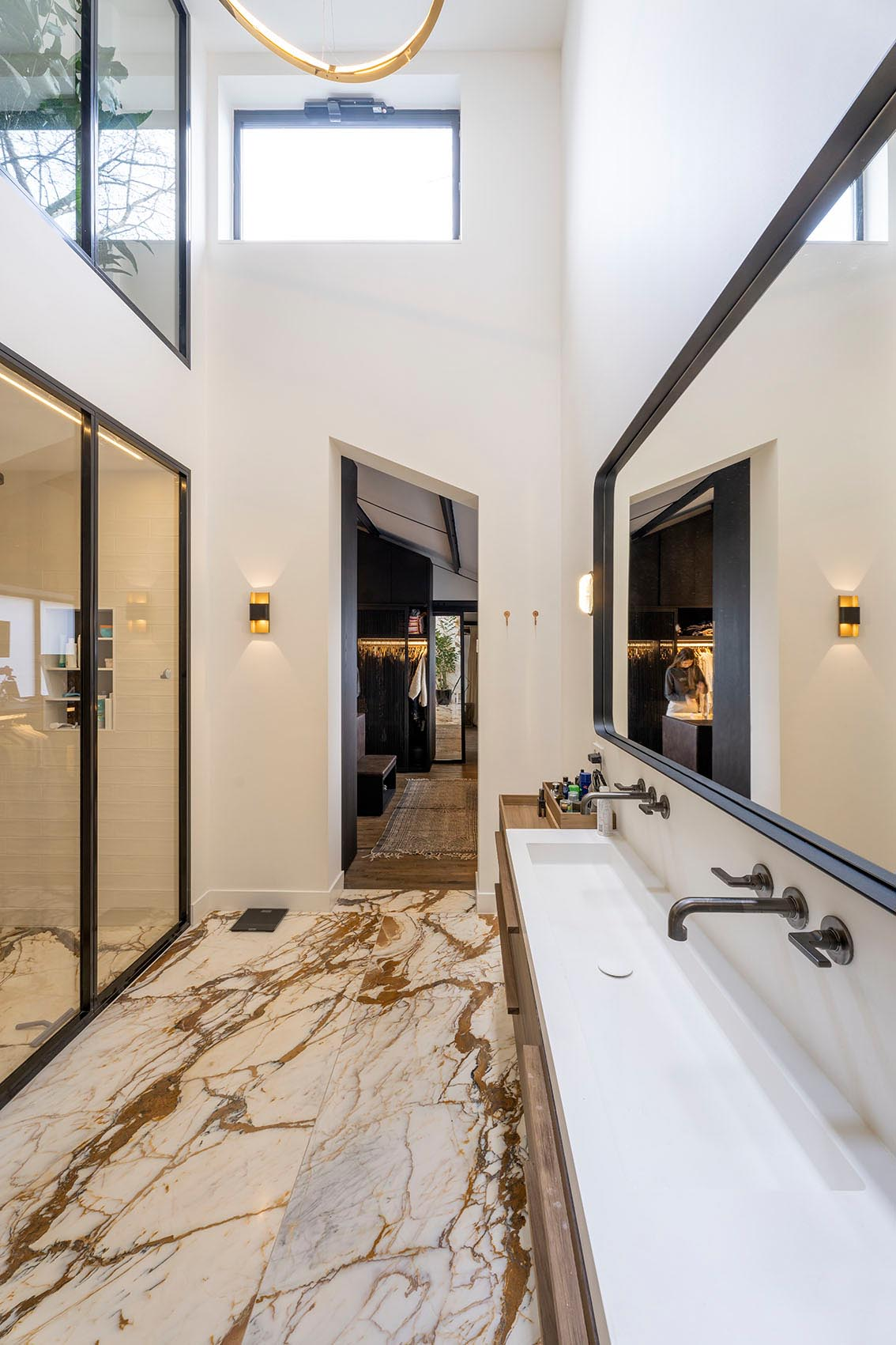 A modern bathroom with a glass-enclosed shower and a long thin vanity with a trough sink.