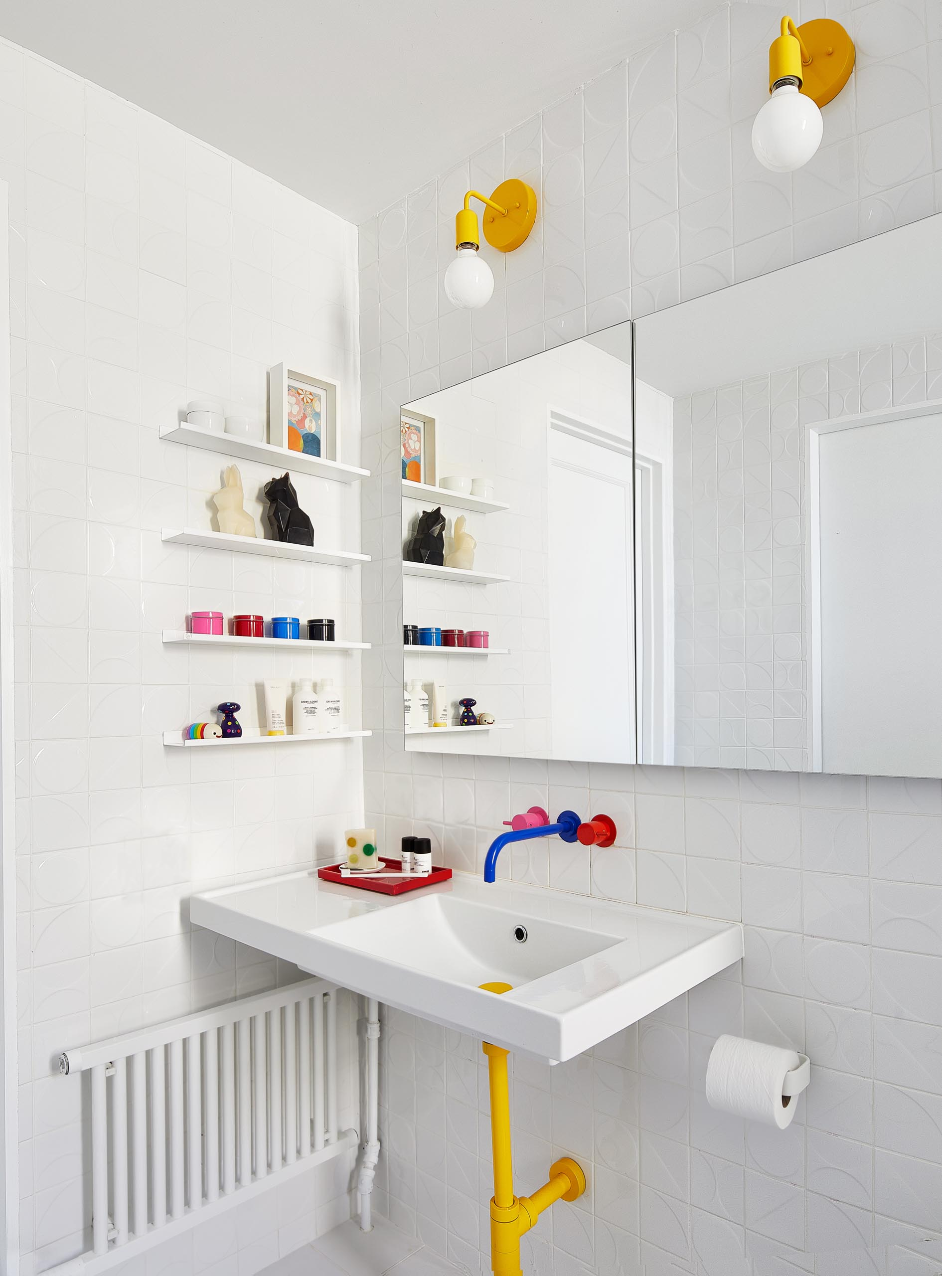 In this kids' bathroom, mix-and-match hot pink, yellow, and blue plumbing fixtures by VOLA join dimensional wall tiles by Kho Liang and yellow lighting fixtures from Barn Lighting.