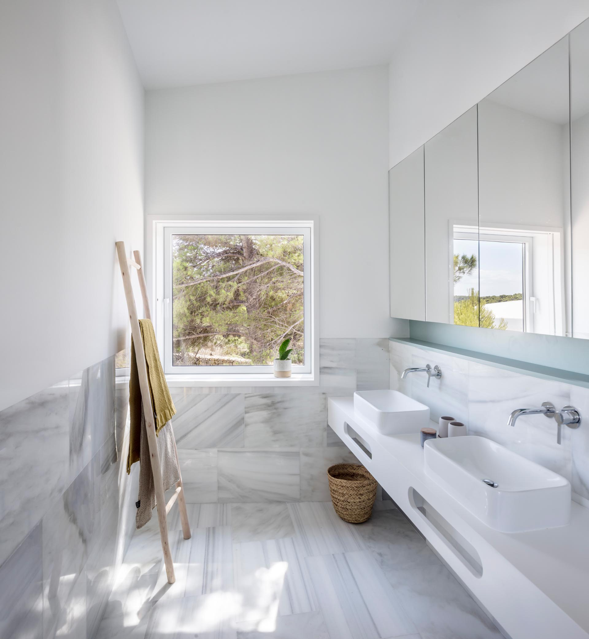 A modern bathroom with large format marble tile, a white vanity, and a pastel turquoise shelving niche.