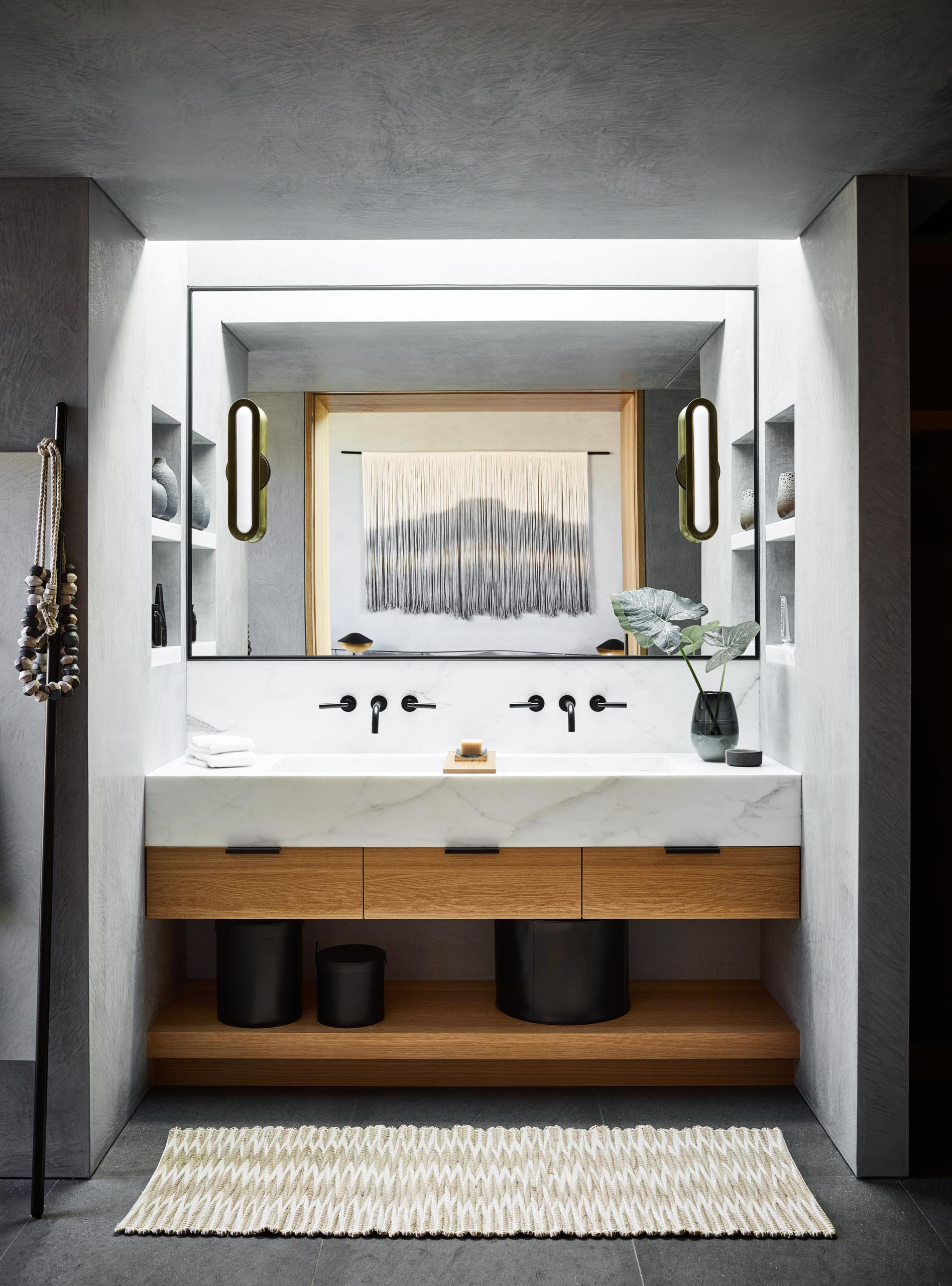 In this modern bathroom, a skylight shines down on the vanity, while shelving niches have been positioned on either side
