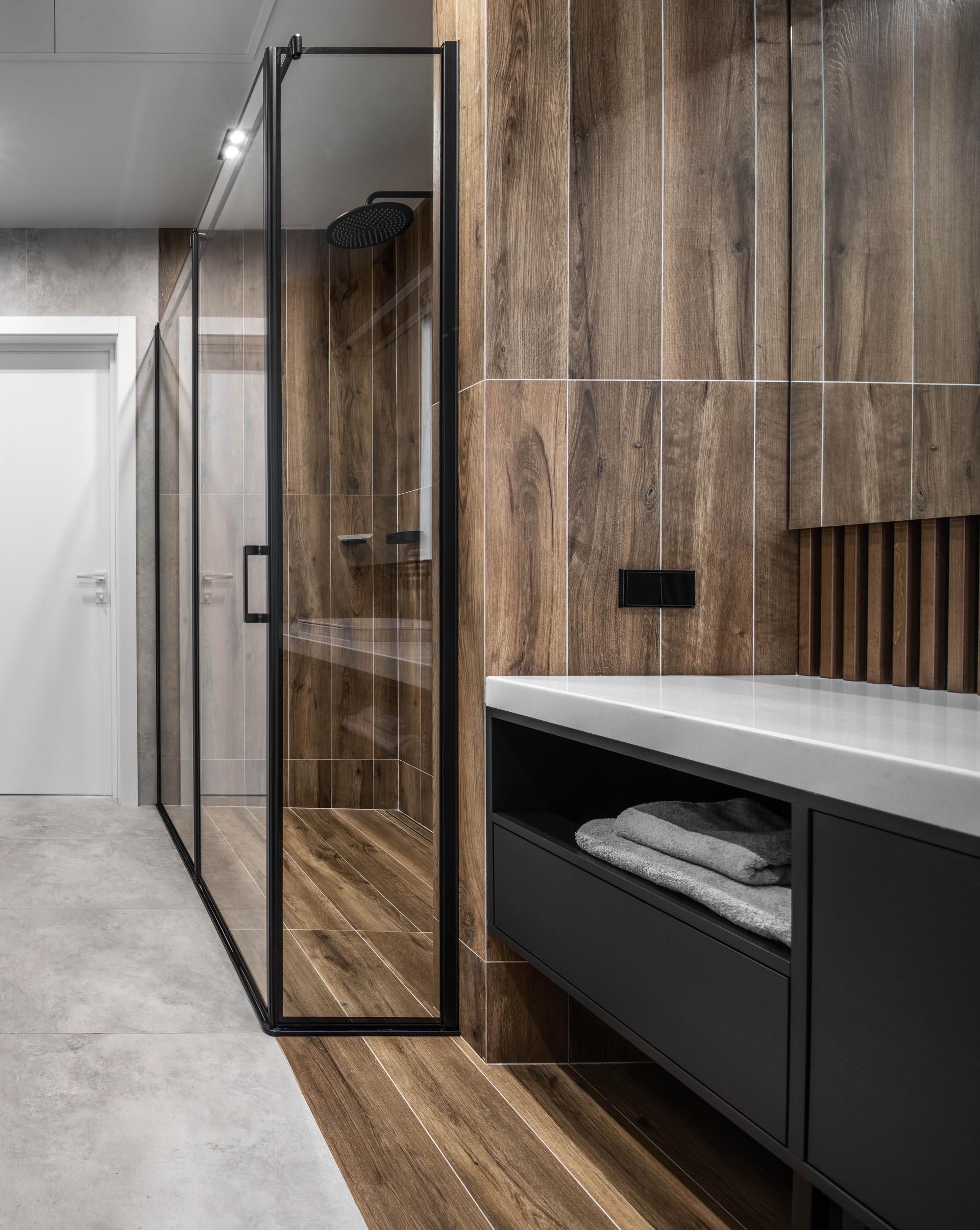 A modern bathroom with black vanity and wood-like ceramic tiles.
