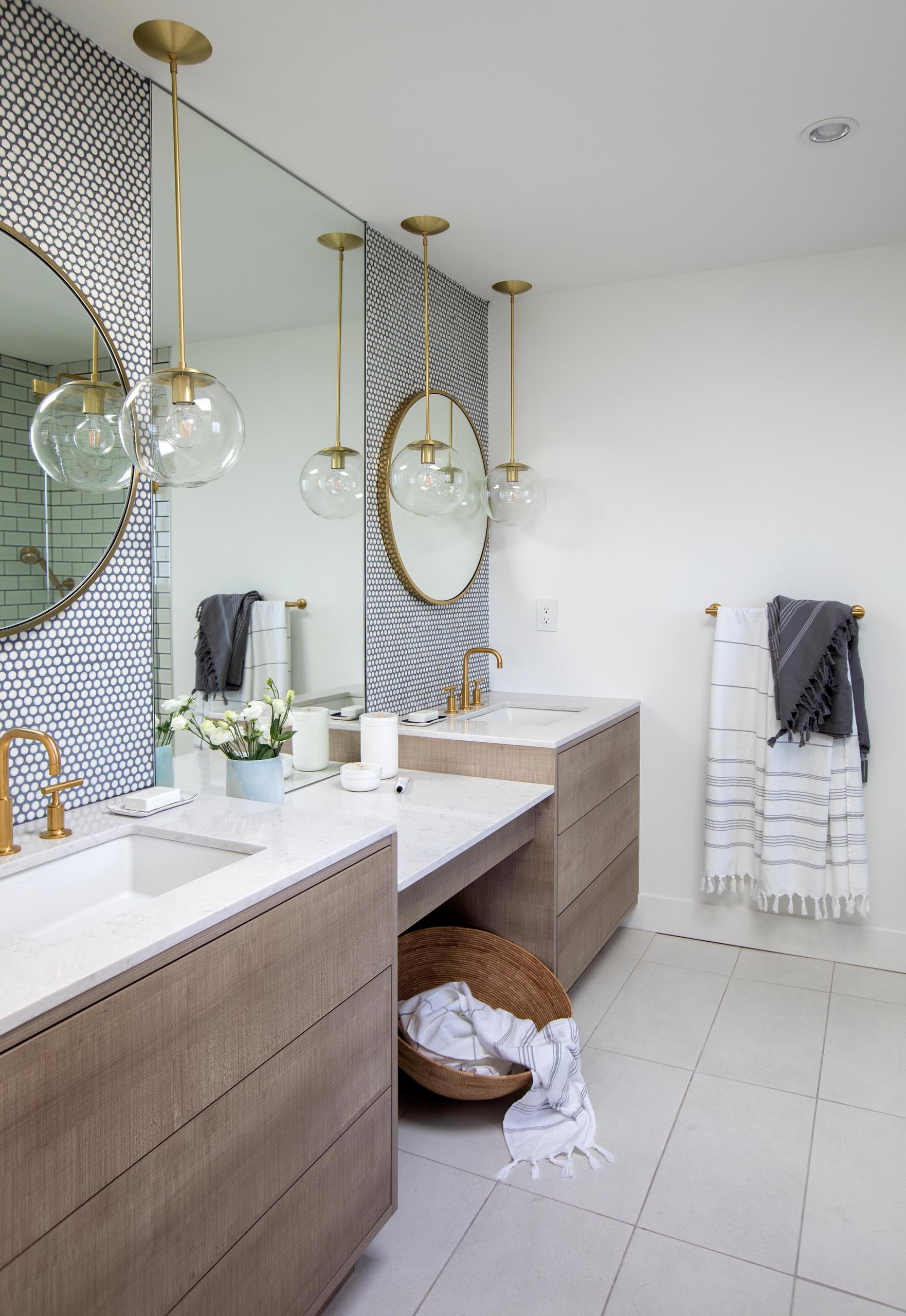 This modern master bathroom includes penny tile with dark grout, a wood vanity with a drop down countertop between the sinks.
