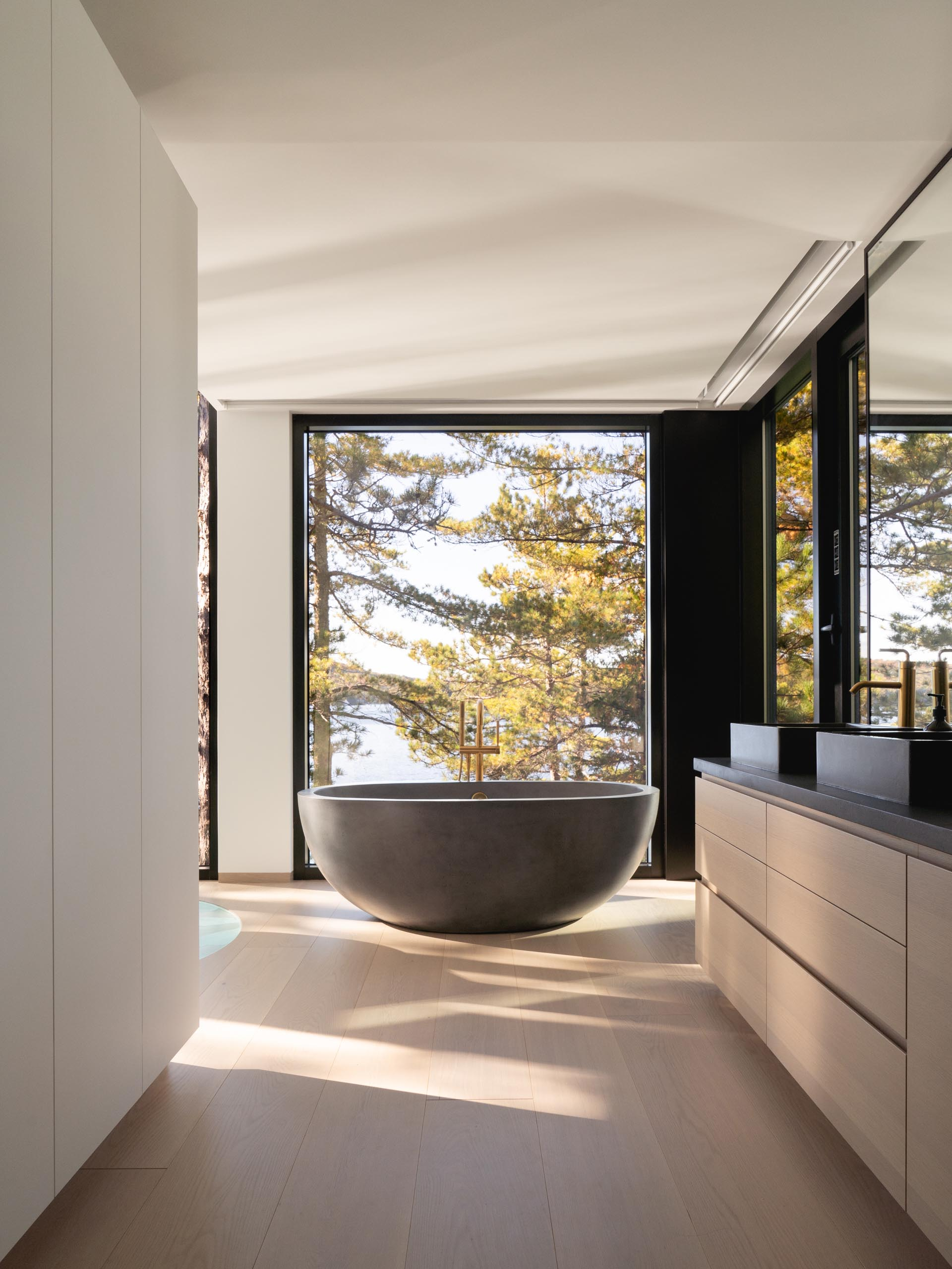A modern en-suite bathroom with a freestanding bathtub in front of the window, and a minimalist wood vanity with dark countertop.