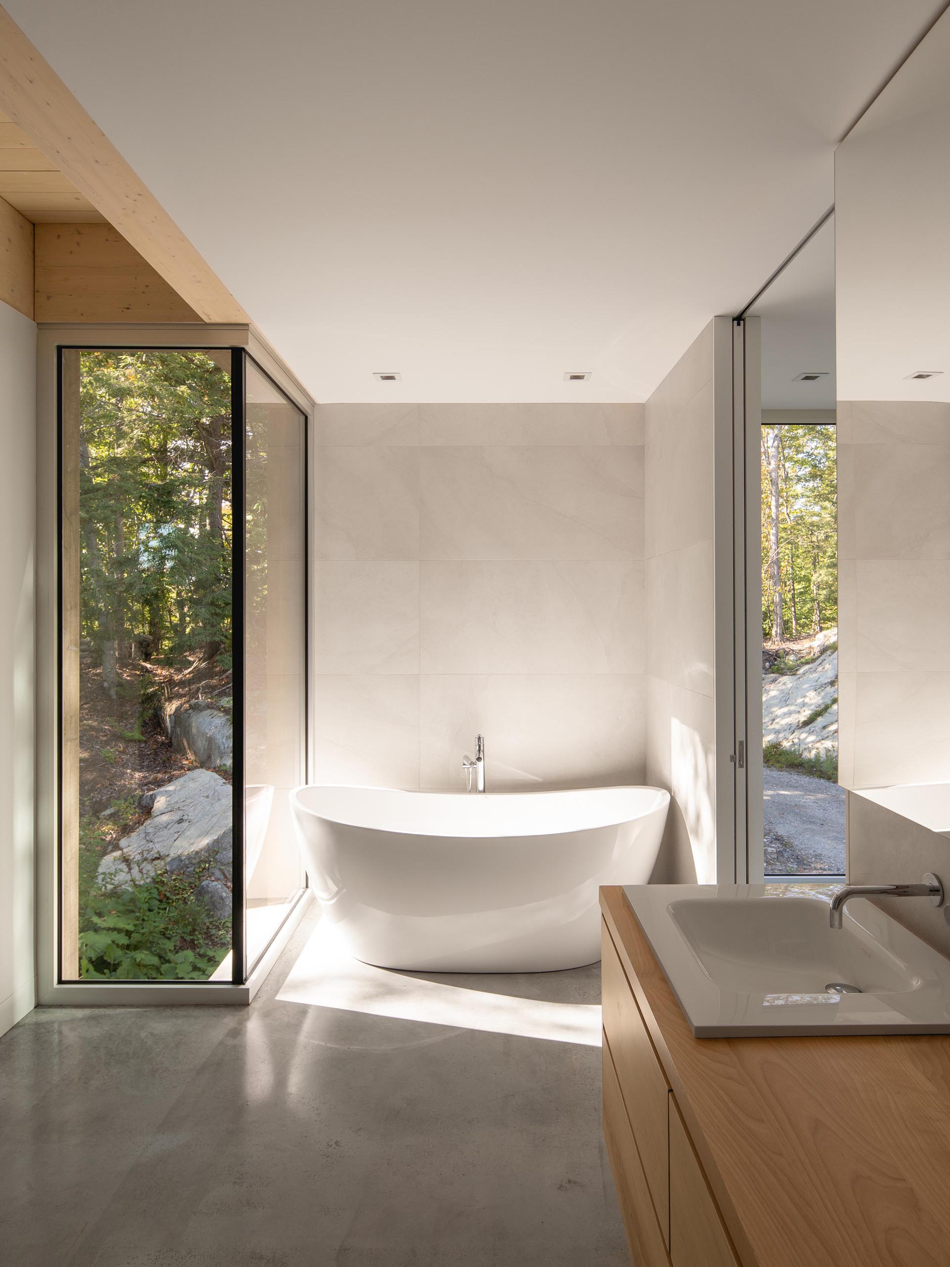 In this modern bathroom, there's a freestanding bathtub with forest views, while a wood vanity adds a natural element.