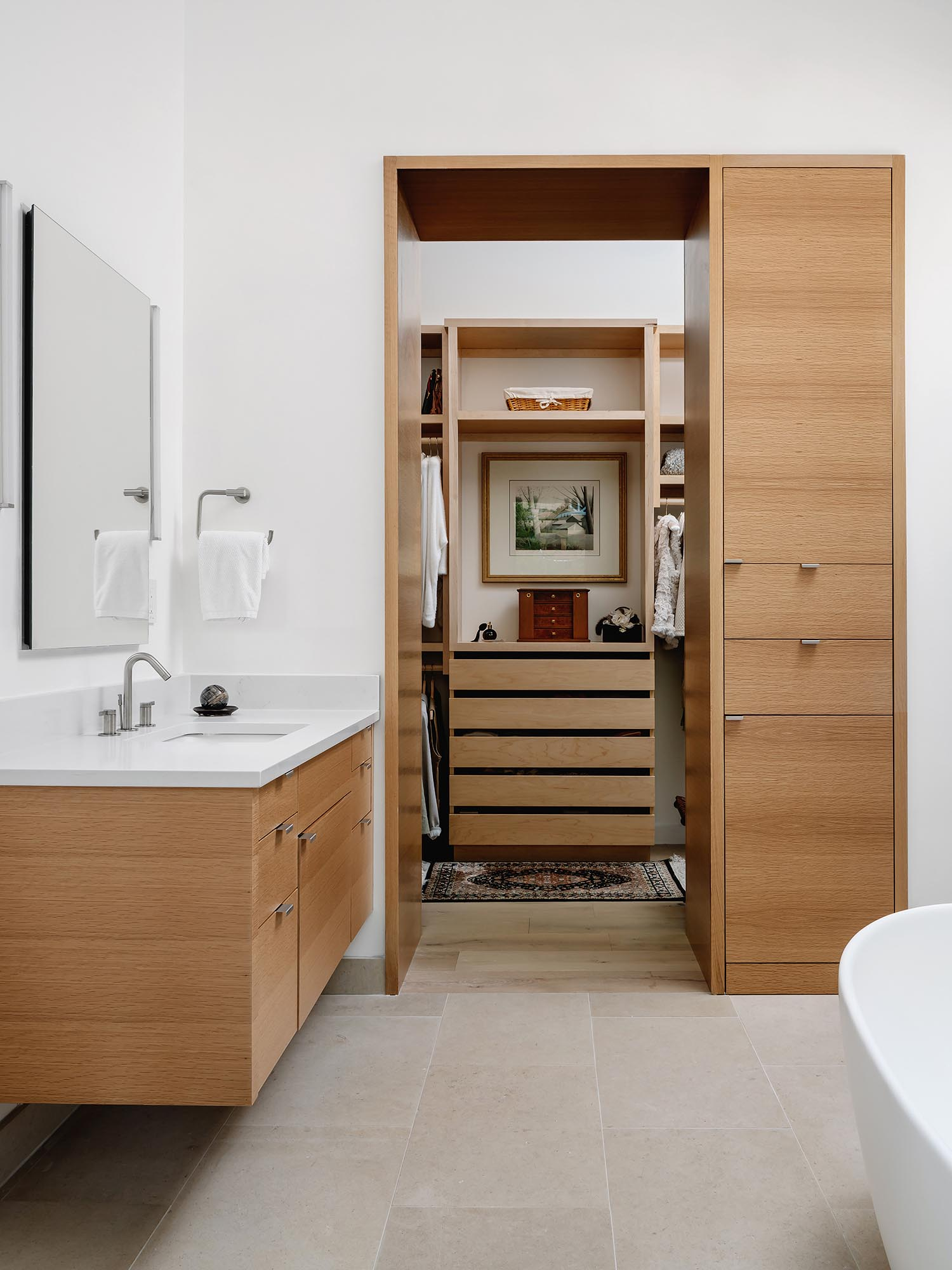 The en-suite bathroom, which has a walk-in closet attached, includes a freestanding bathtub, separate vanities, and limestone on the floor and wall.