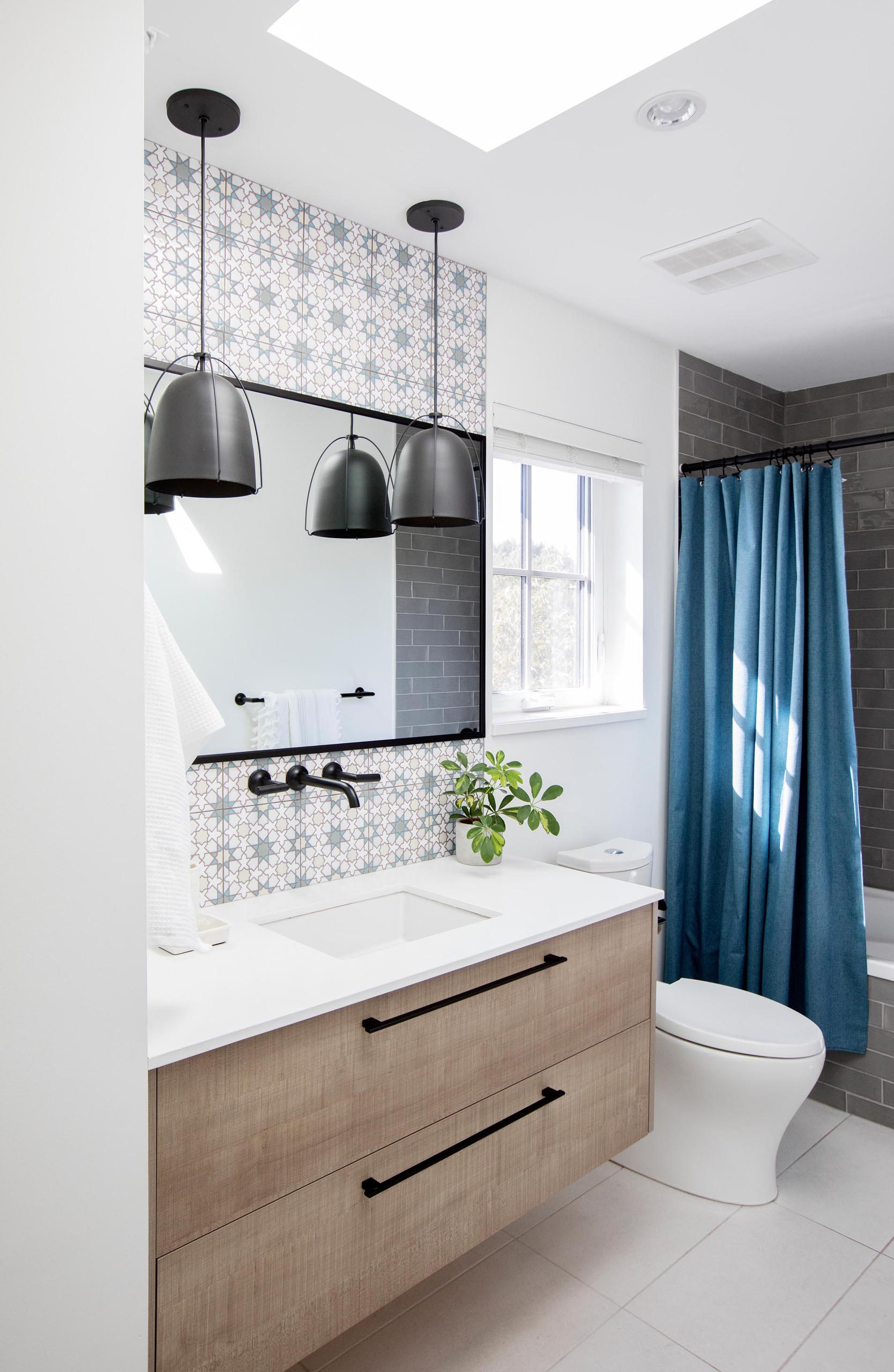 In this modern bathroom, patterned tiles have been used to designate the vanity area, while black pendant lights complement the black mirror frame and shower curtain rod.