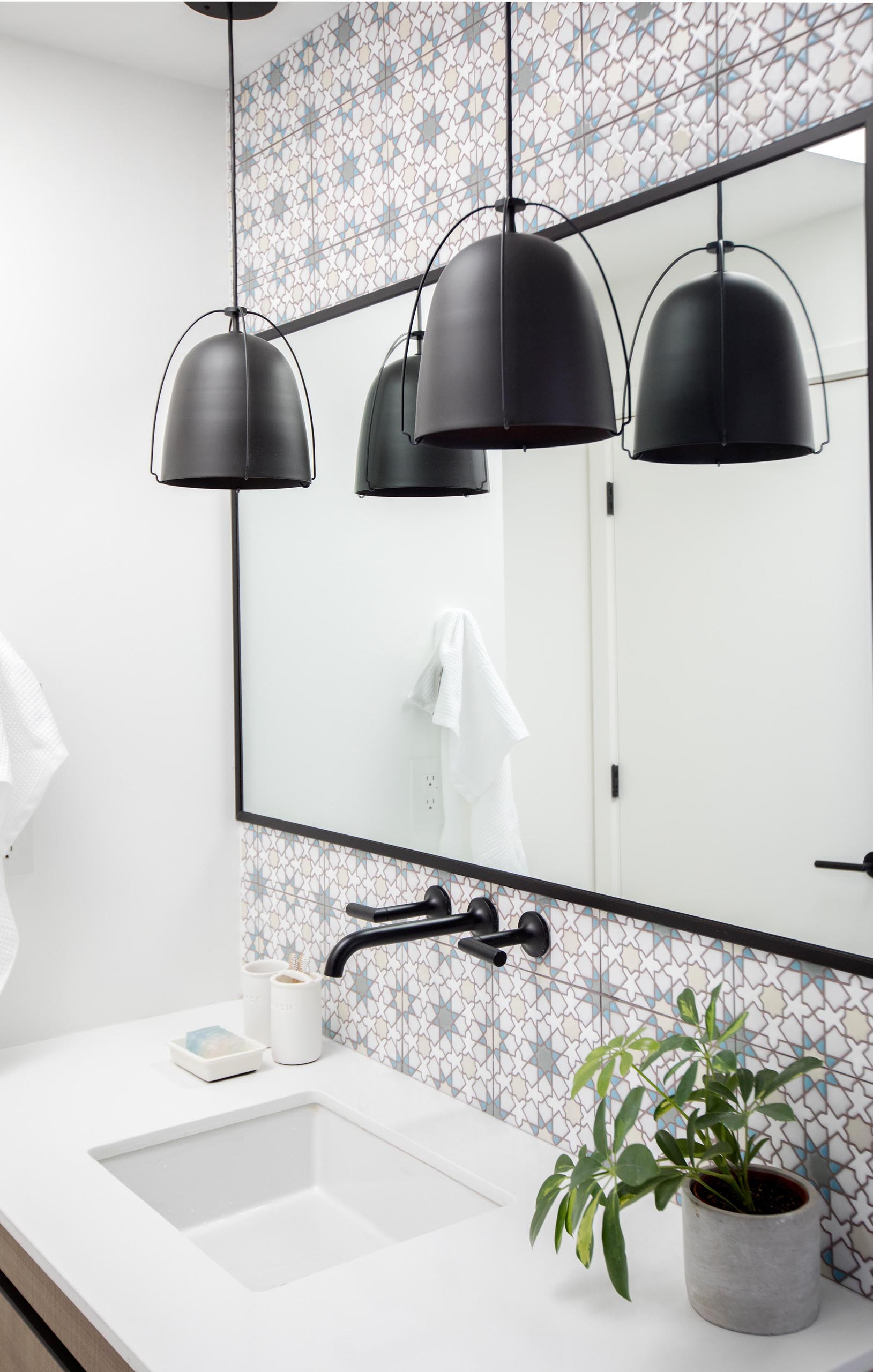 In this modern bathroom, patterned tiles have been used to designate the vanity, while black pendant lights complement the black mirror frame and shower curtain rod.